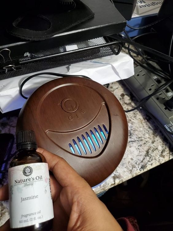 reviewer photo of the air purifier and the jasmine oil they use with it