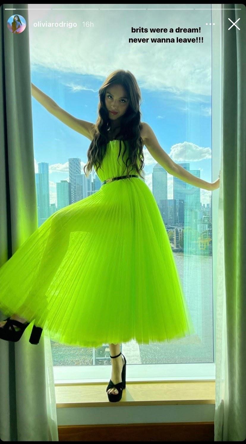 olivia rodrigo in a neon green dress posing in a window on her instagram story