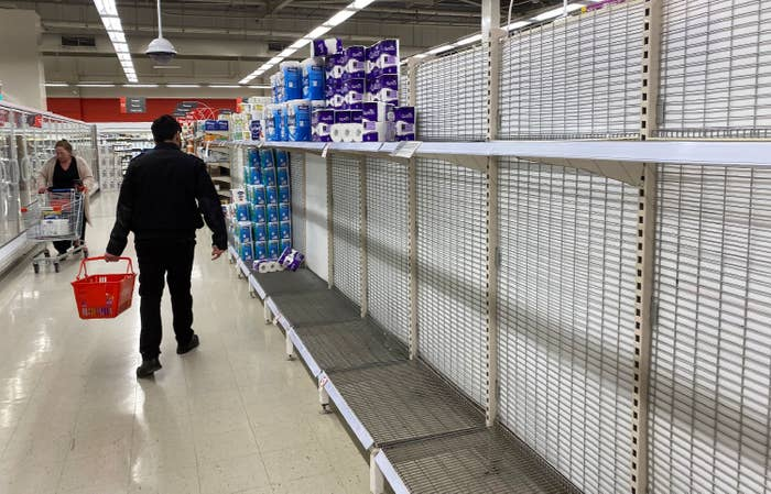 A man walking through a store with empty shelves
