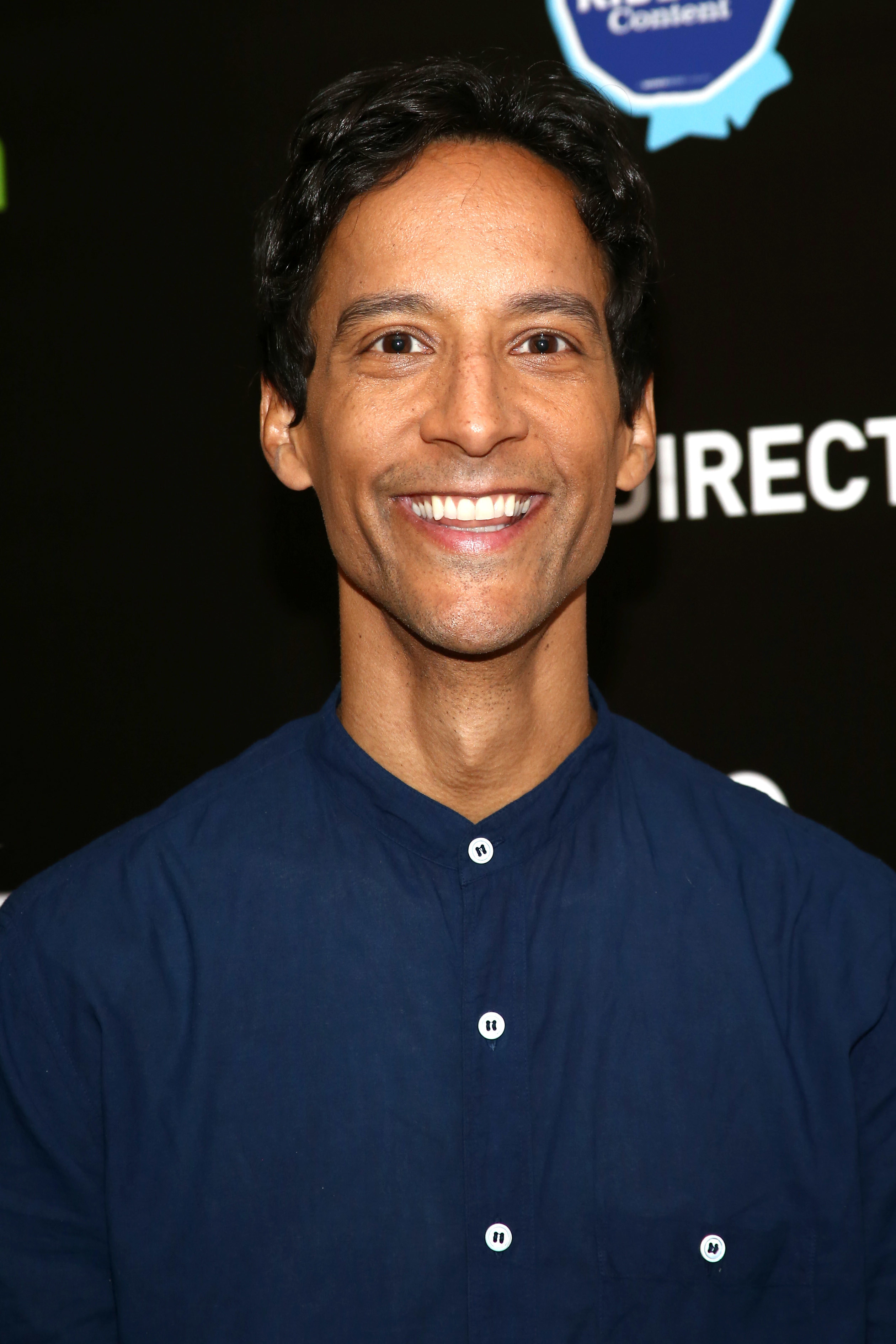 Danny Pudi smiles in a casual, navy blue button-down