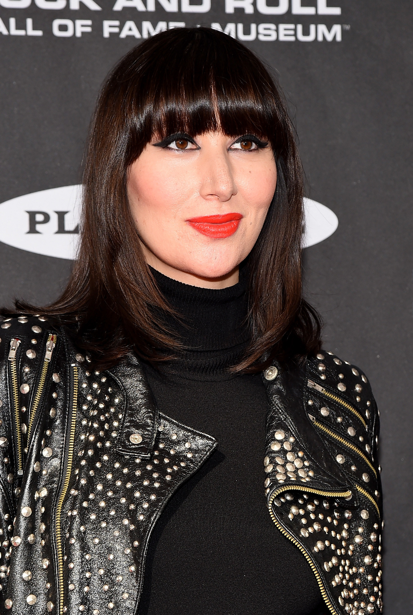 Karen O smiles with a bold red lipstick, black turtleneck, and leather jacket
