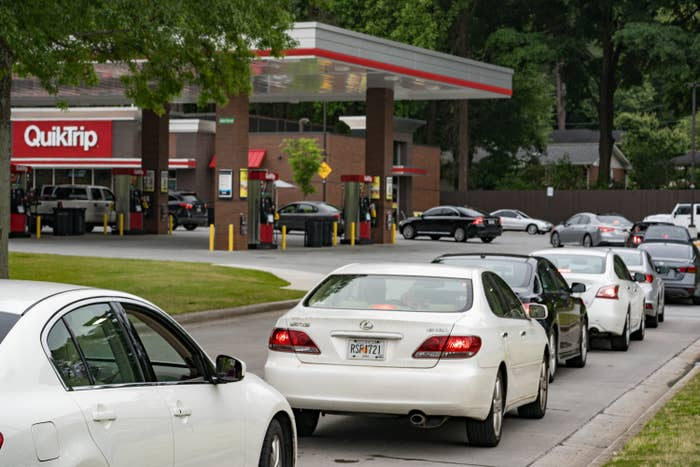 A long of cars of people waiting to get gas