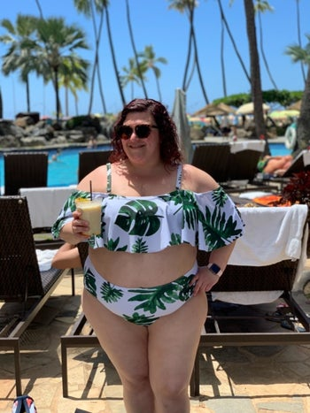 Reviewer wearing the green and white leaf print ruched two-piece with flounce detail