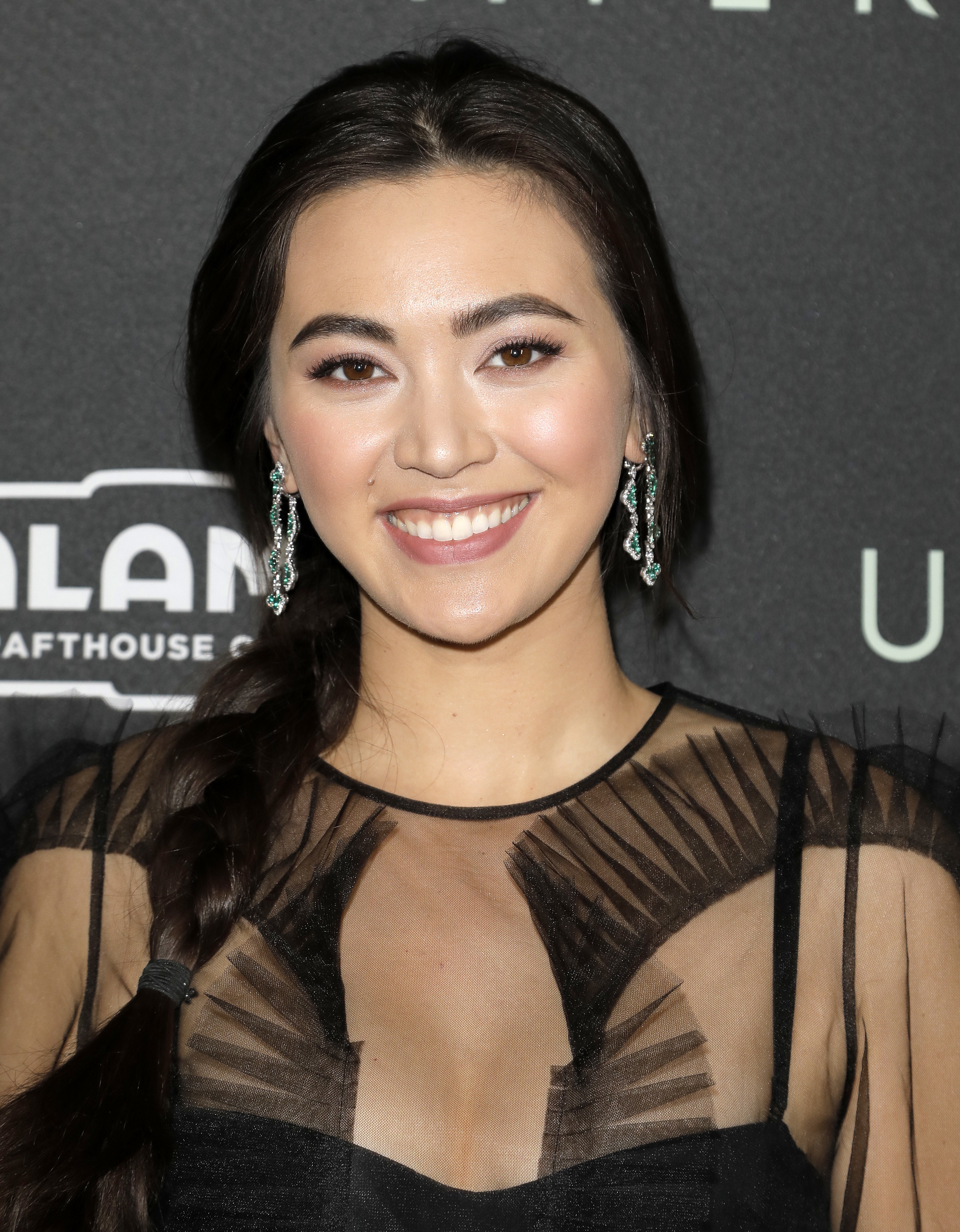 Jessica Henwick smiles with her hair in a low ponytail, wearing a chiffon black dress