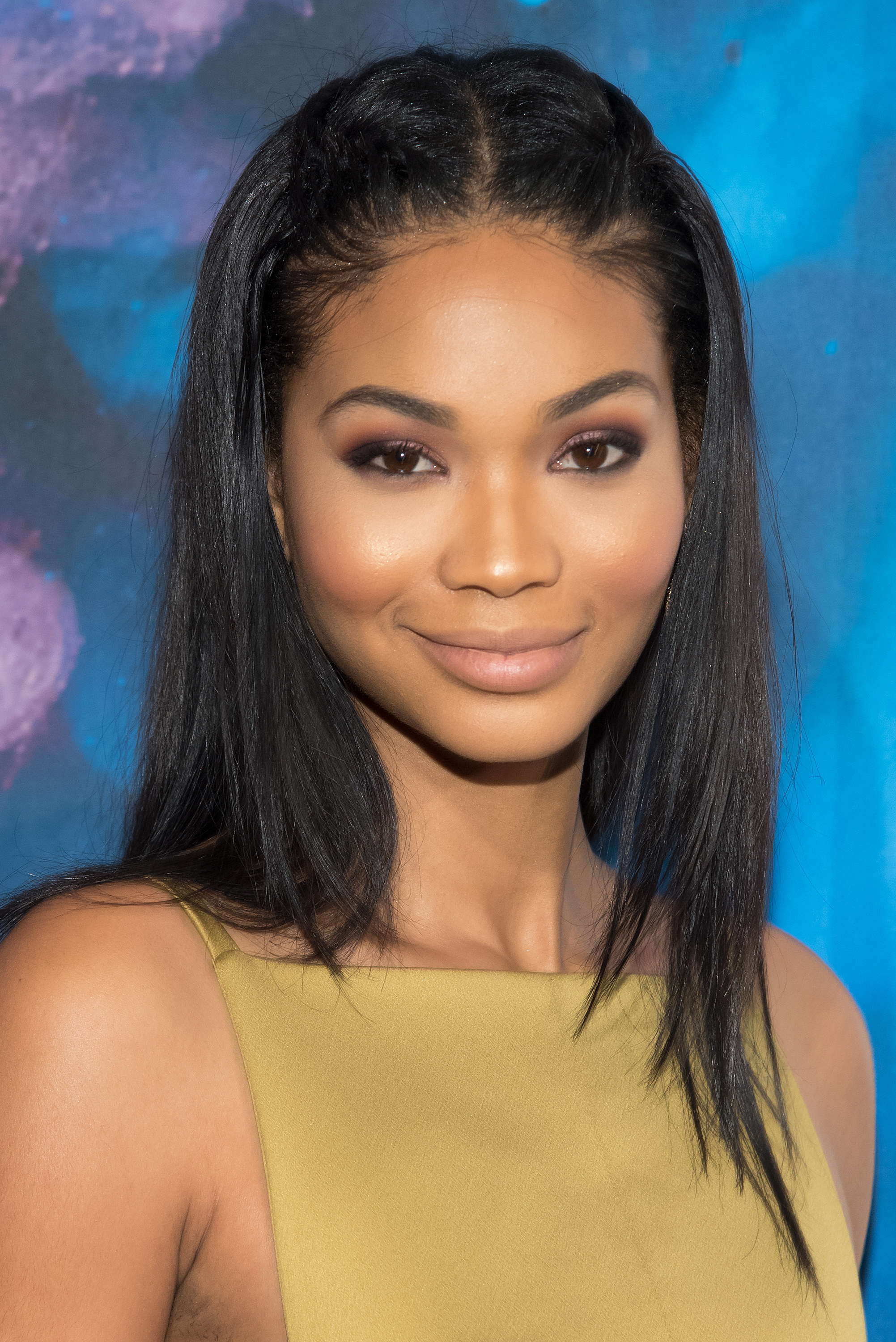 Chanel Iman smiles with her hair straightened and pinned back, in a muted, olive-yellow dress