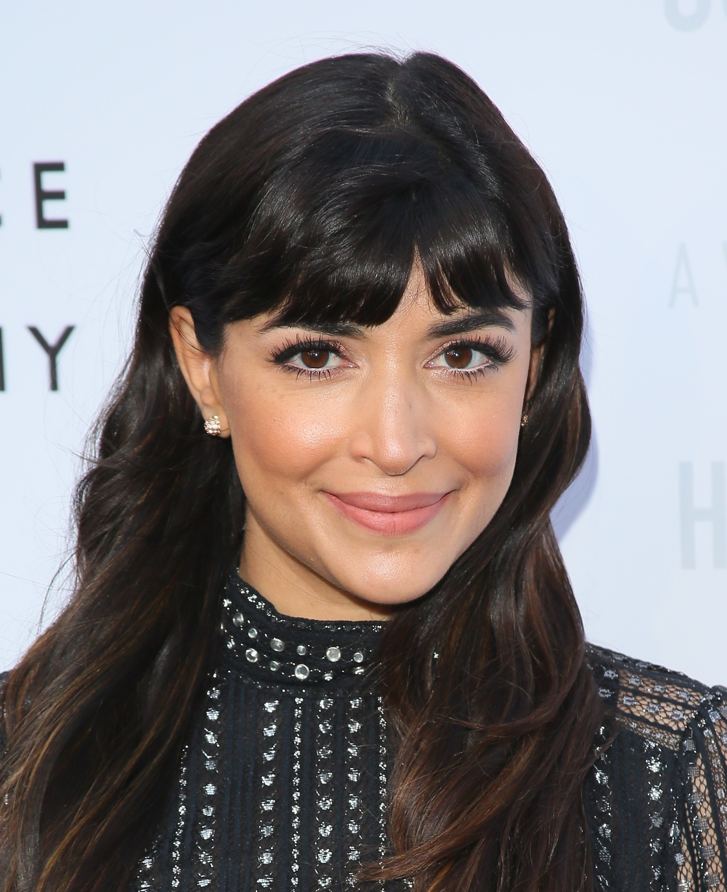 Hannah Simone wears a jeweled black dress with a high collar and her hair down in slight waves