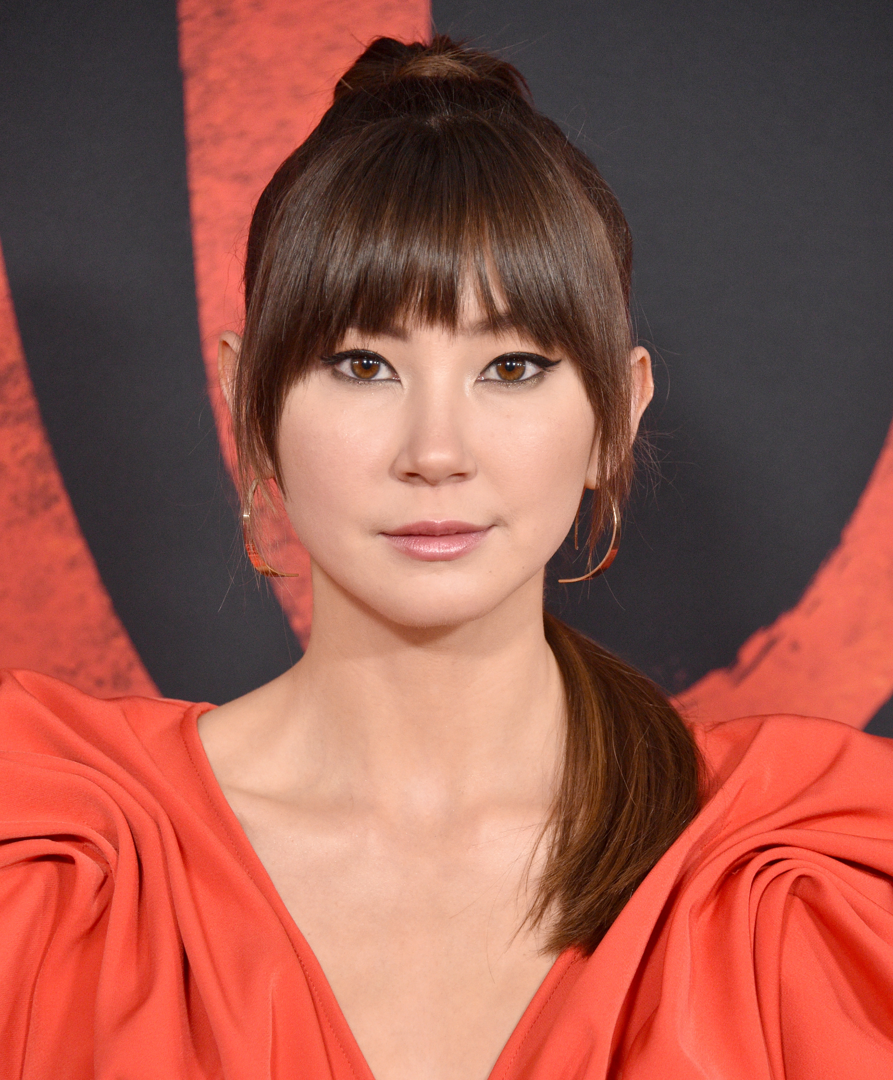 Kimiko Glenn wears a deep-cut, coral dress with ruched-shoulder, and her hair in a pony tail while her bangs frame her face