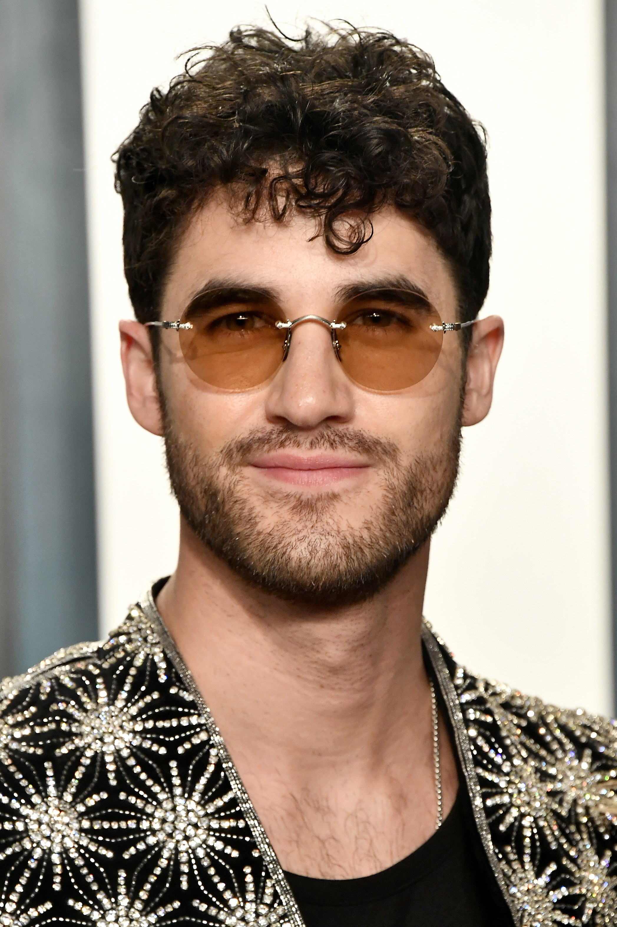 Darren Criss in a beaded blazer and round, brown tinted glasses