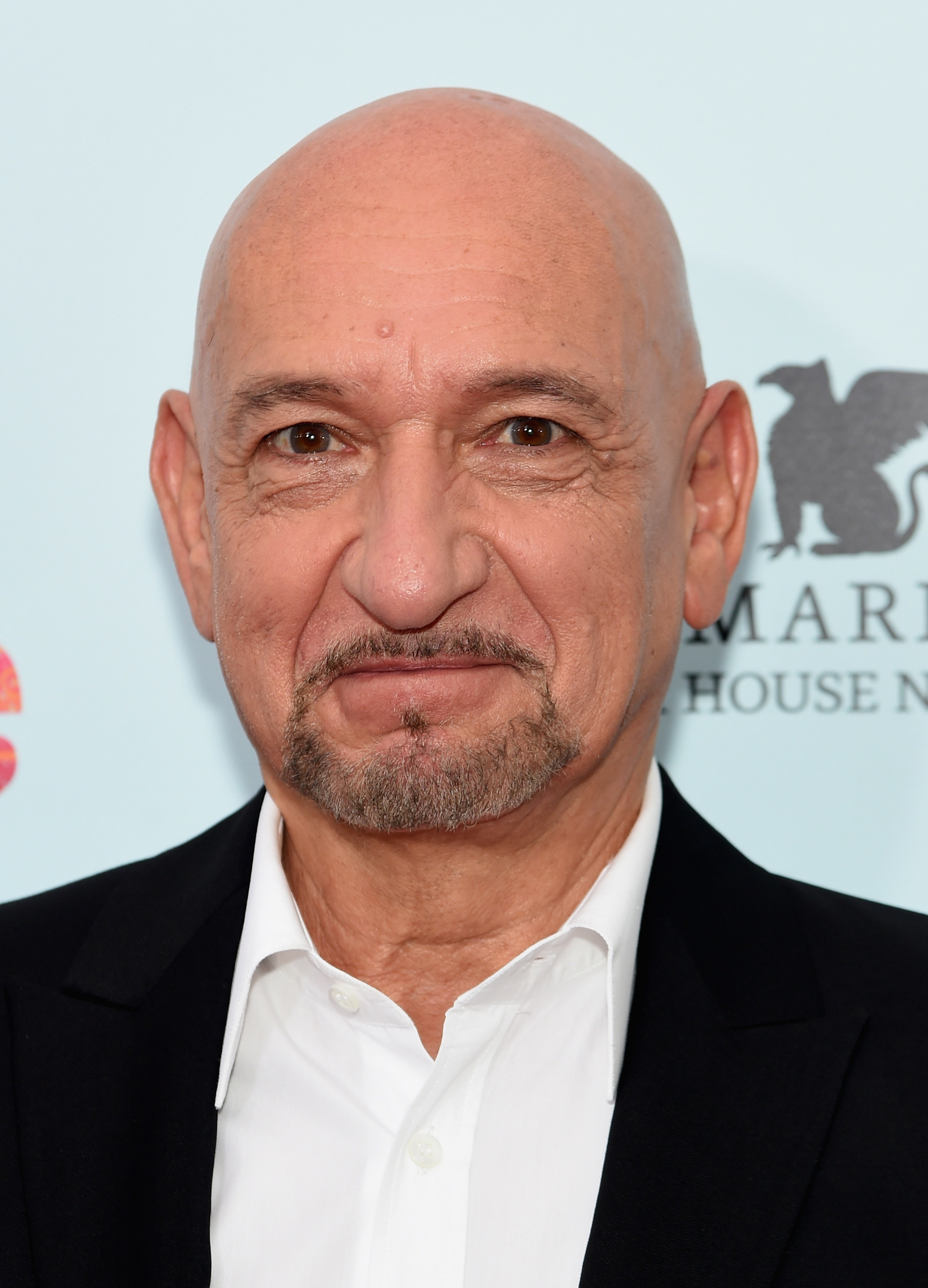 Ben Kingsley wears a white dress shirt with a collarless suit jacket as he smiles at the camera