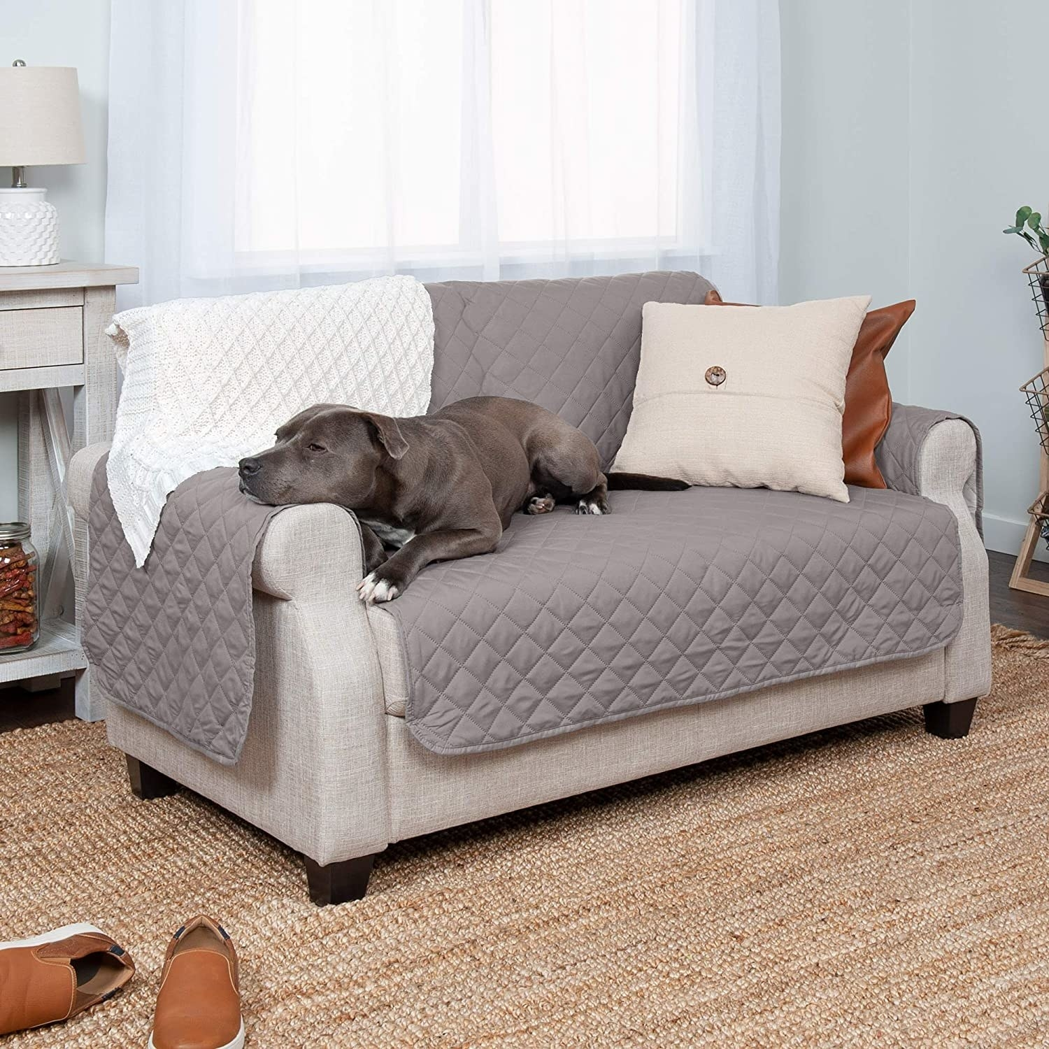 a dog resting on a couch with a couch cover on it
