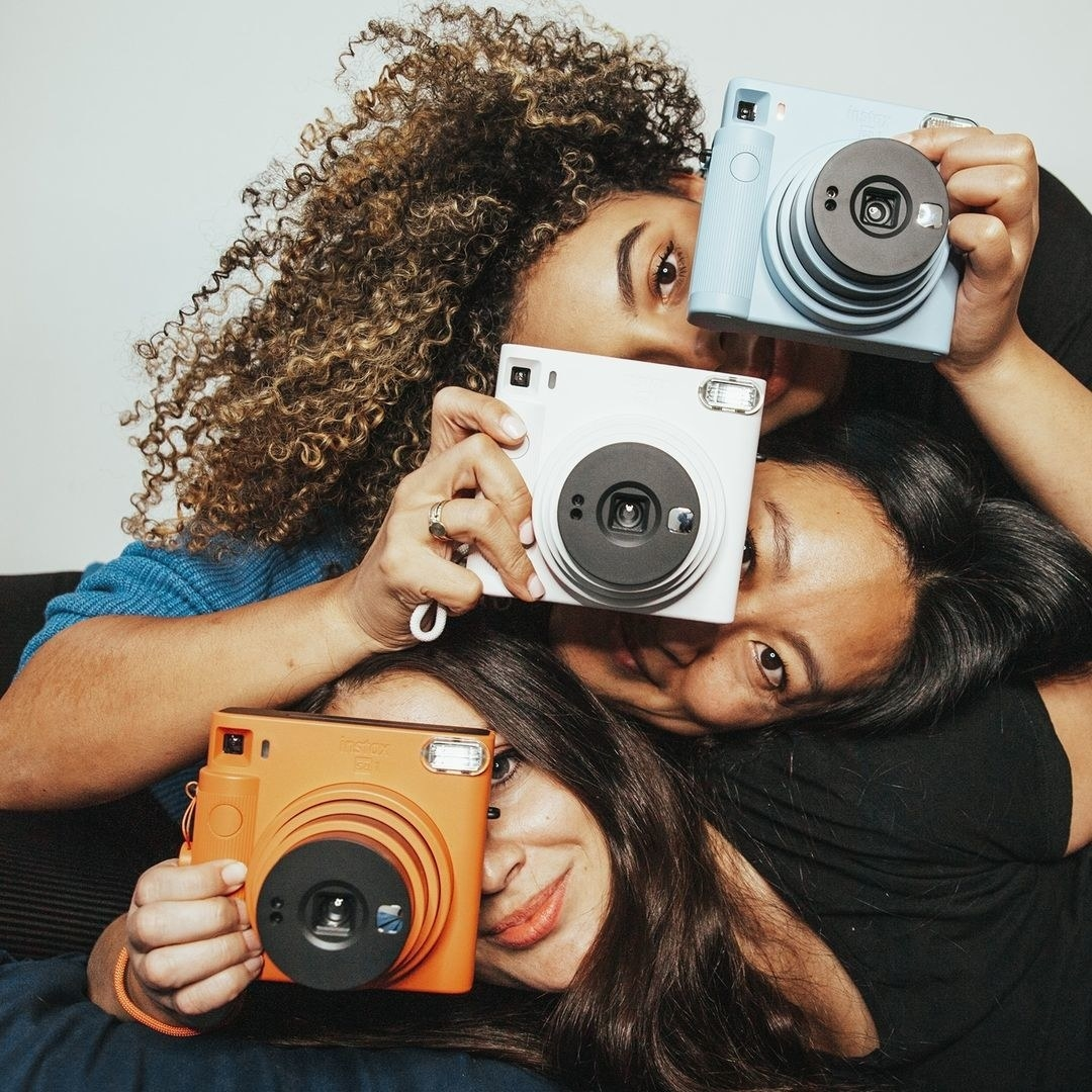 Three people leaning their heads on top of each other and holding instant cameras
