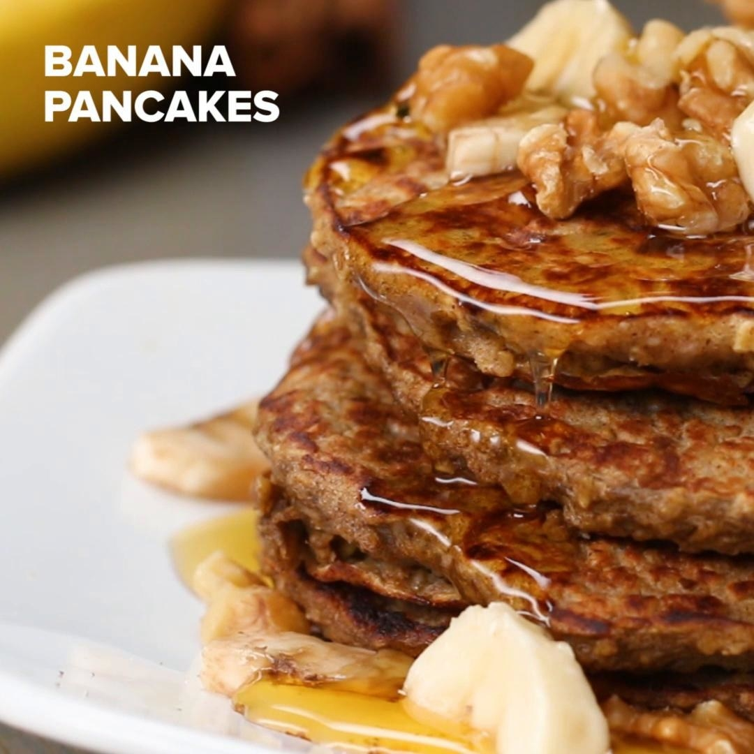 Pancakes topped with syrup, walnuts, and bananas