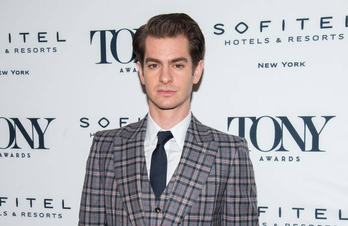 Andrew Garfield posing on a red carpet in a suit