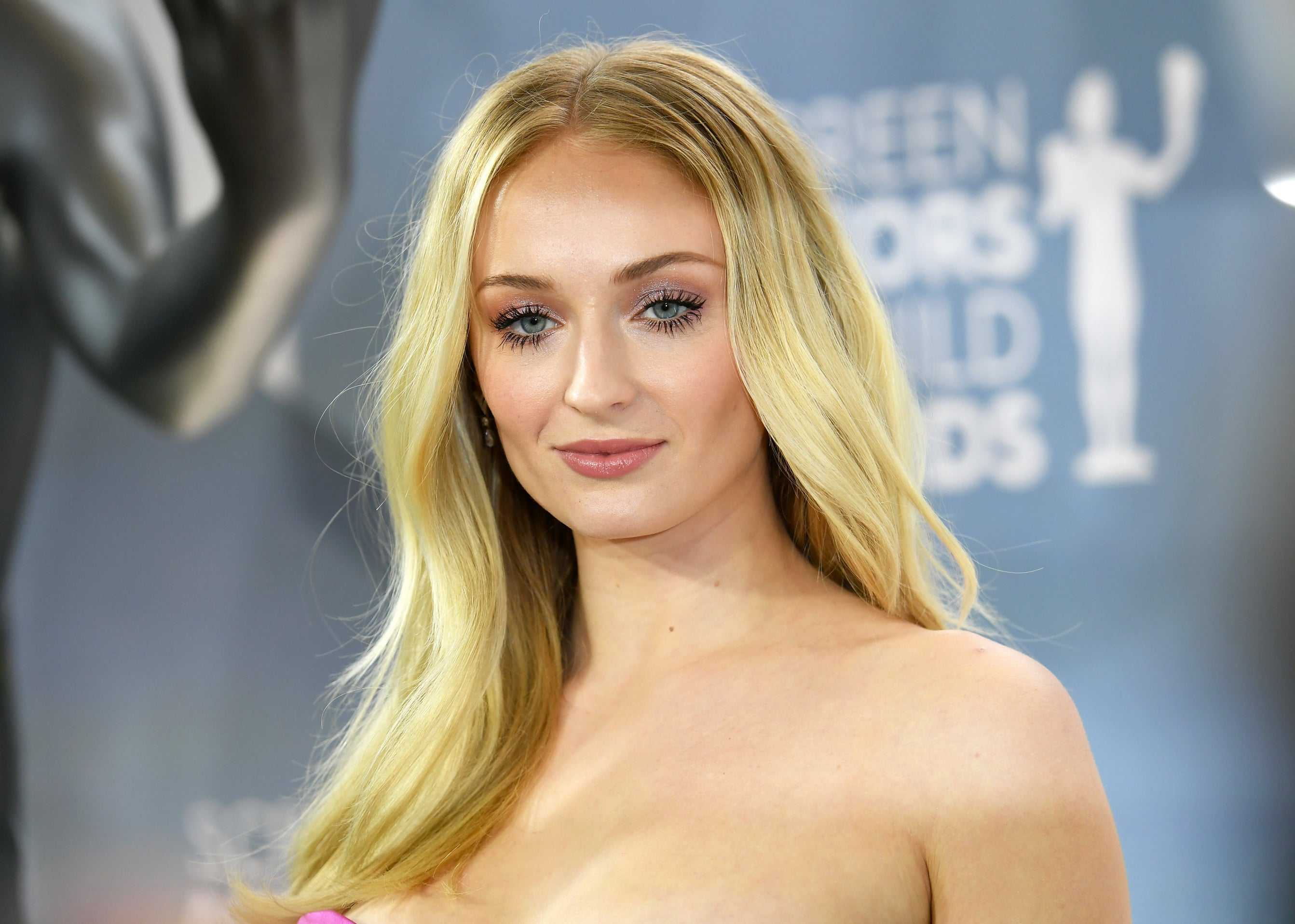 Sophie looks right into the camera in a strapless pink dress at an event