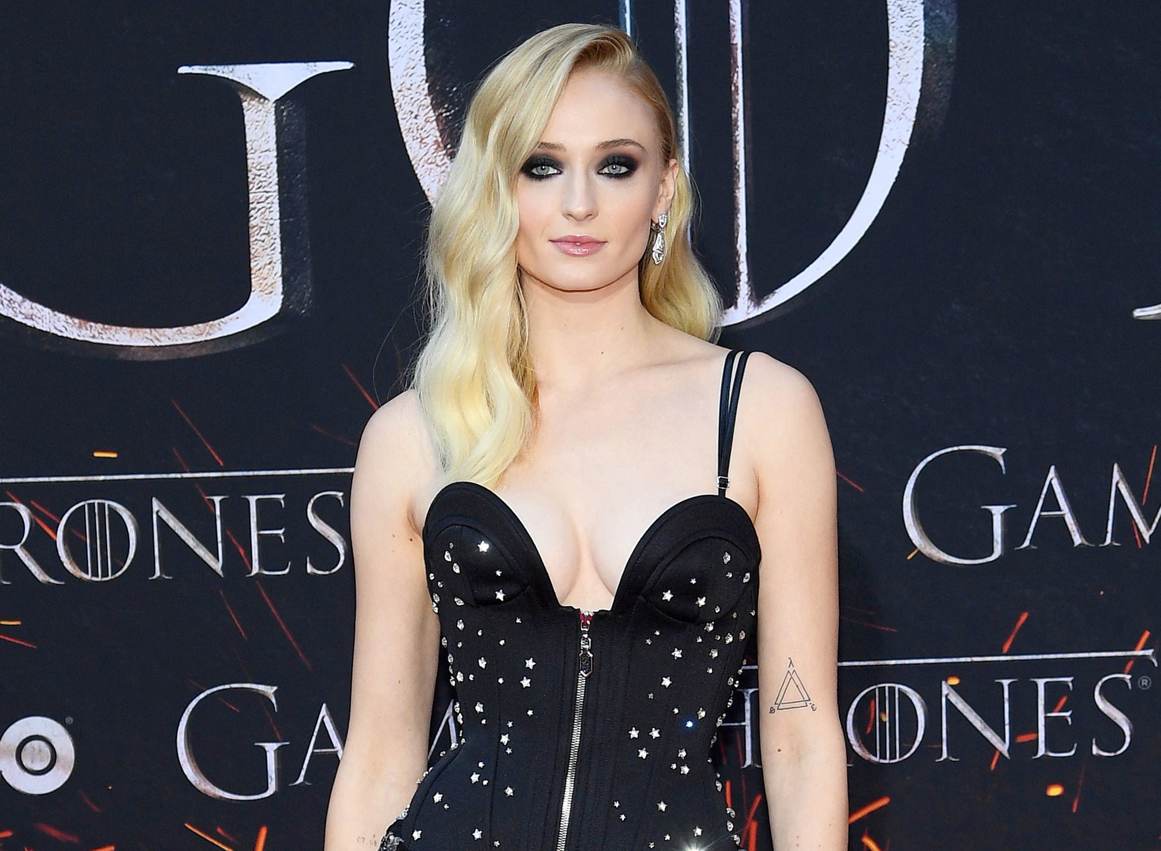 Sophie wears dark makeup and a black dress at a premiere