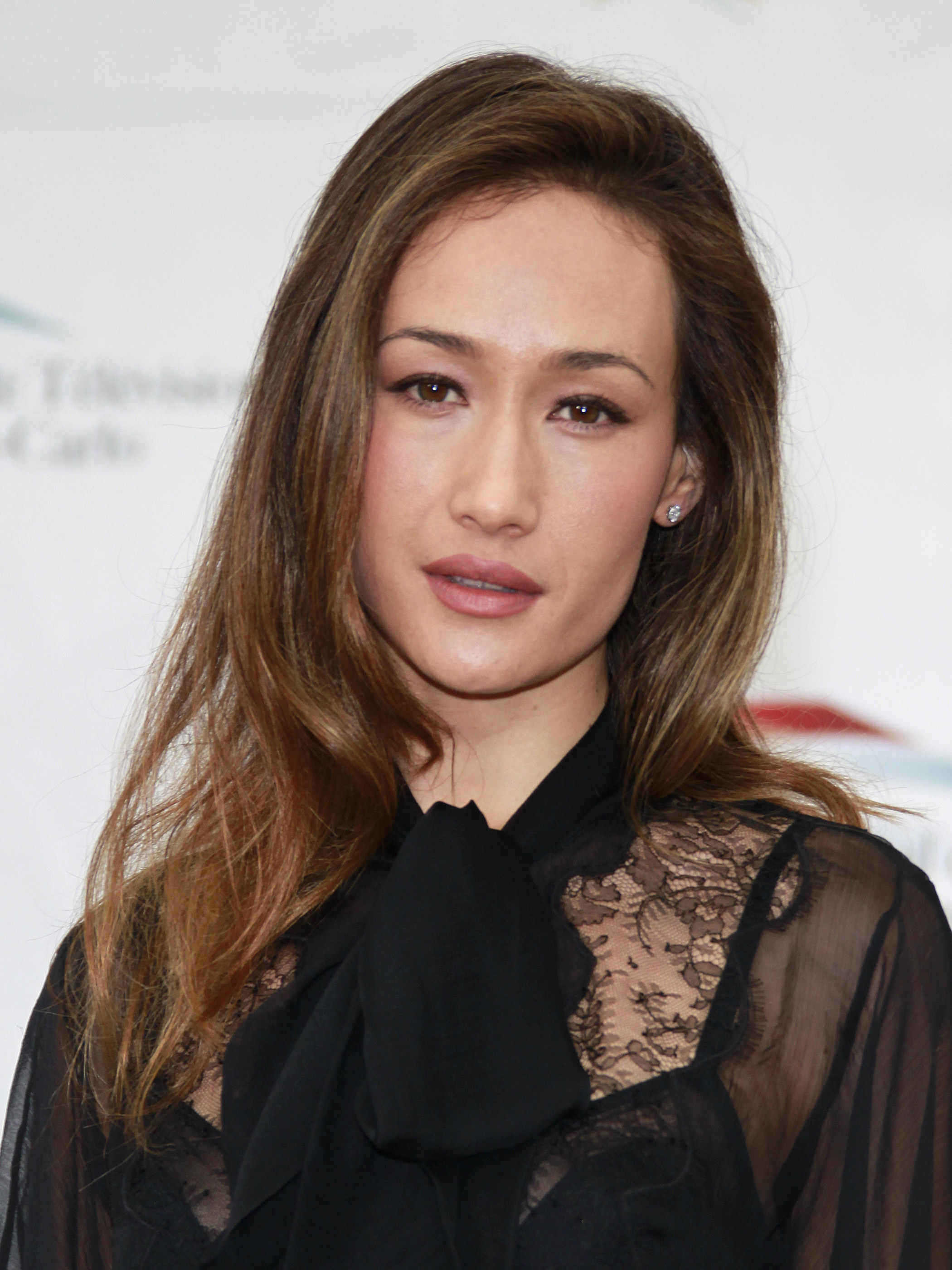 Maggie Q smiles wearing a black, chiffon blouse and neck tie