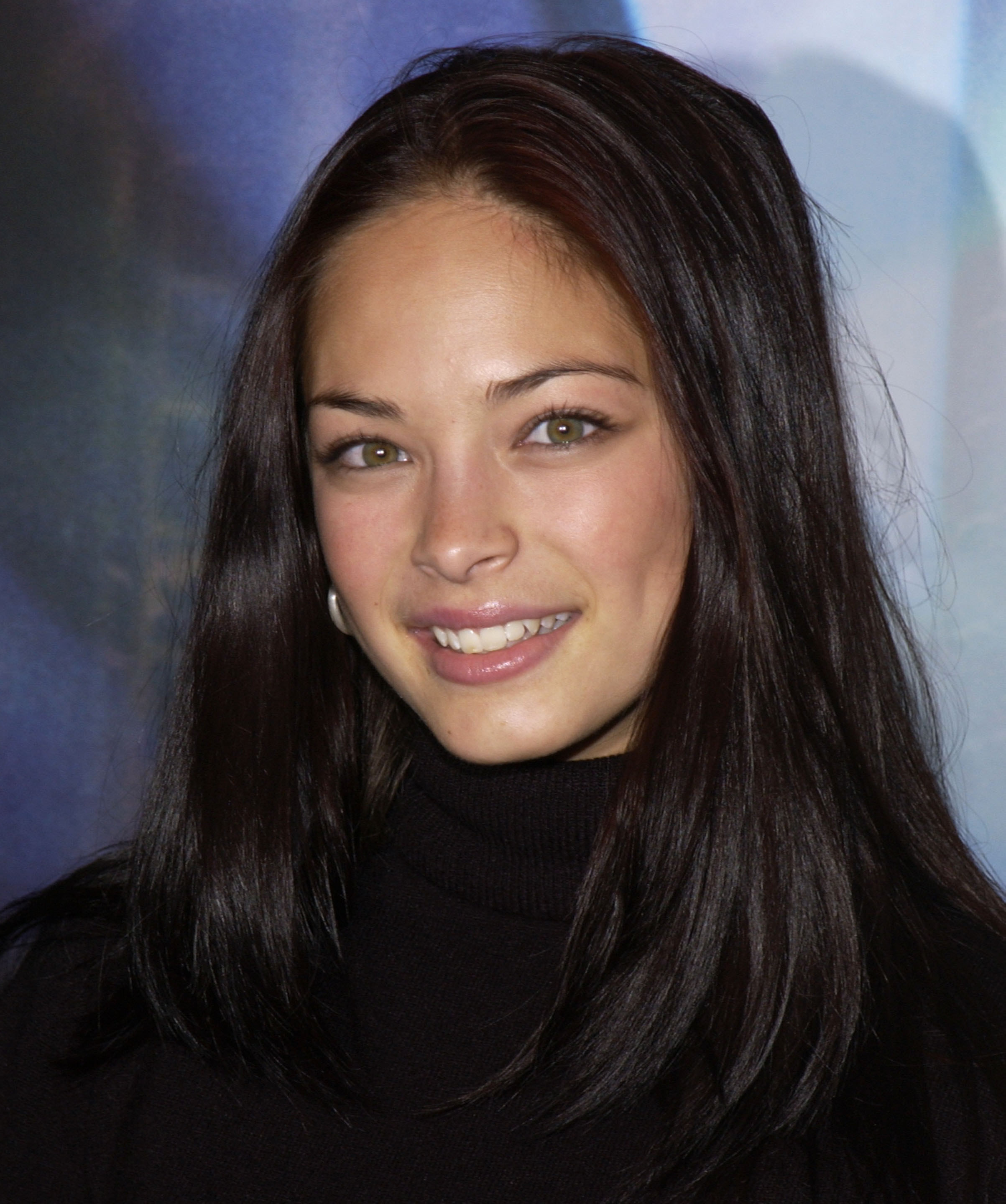 Kristin Kreuk smiles with her hair down and wears a black turtleneck