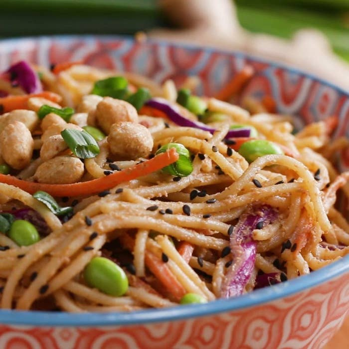 Bowl of noodles topped with peanuts and veggies