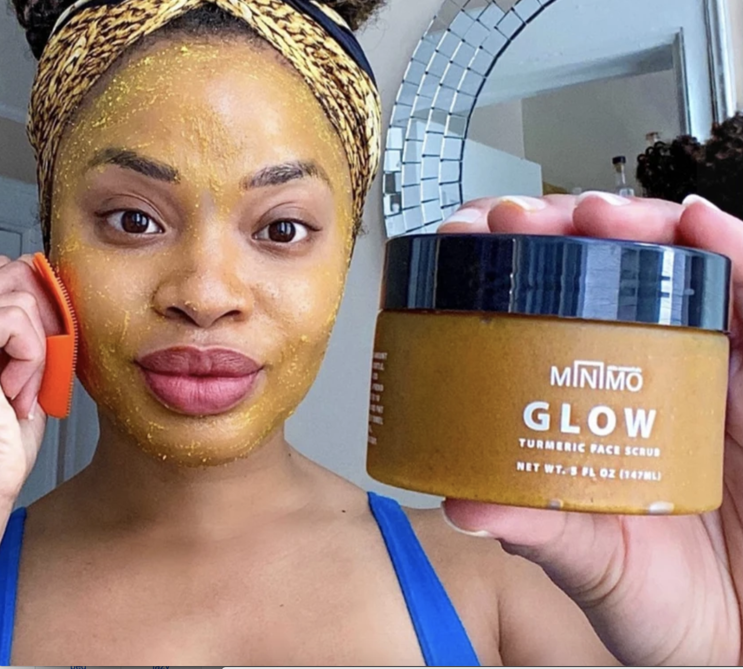 Model with turmeric face scrub on their face, holding the jar of it to the camera