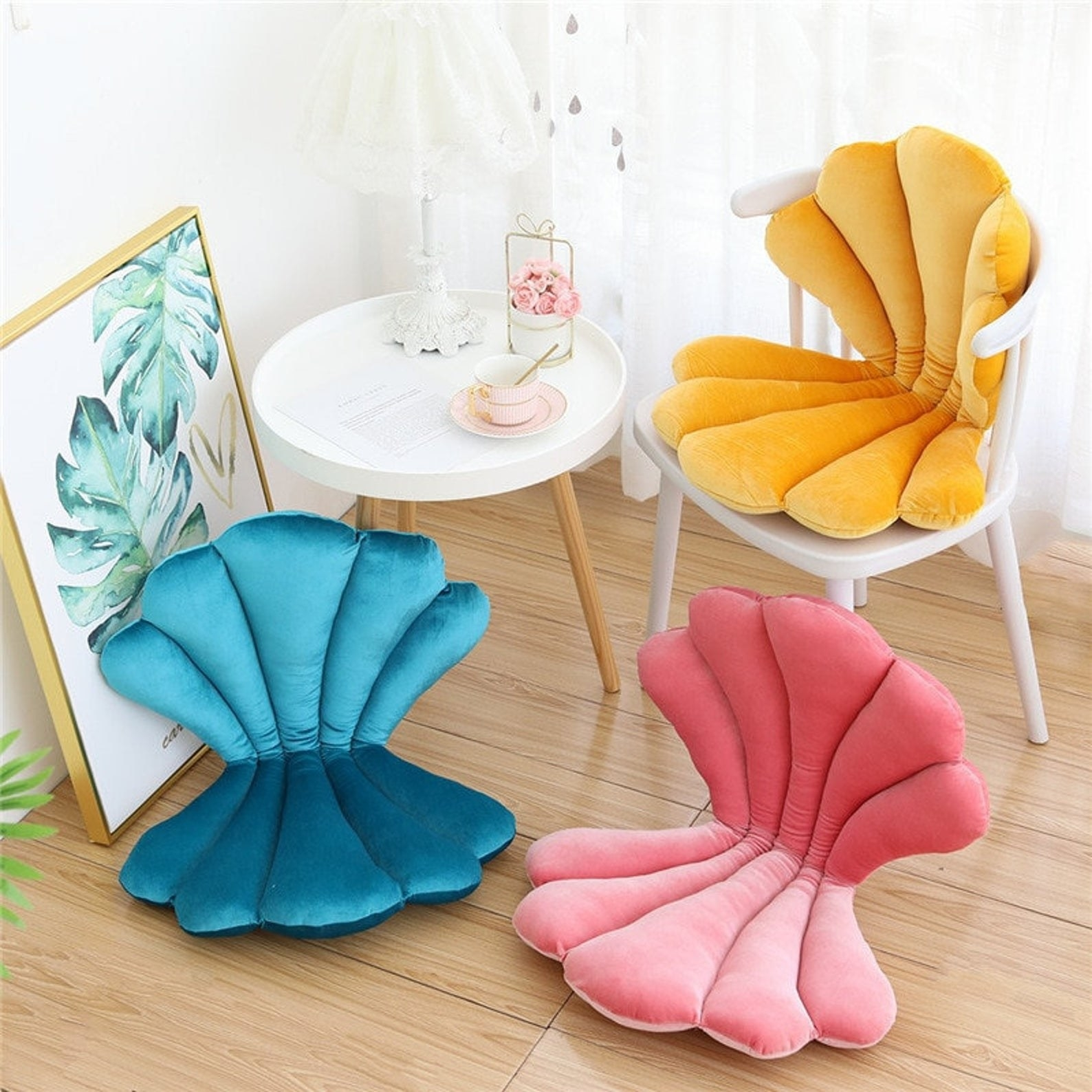 A velvet pillow that's opened like a clam-style seashell so it provides back and butt support. It's in three colors: blue, pink, and yellow