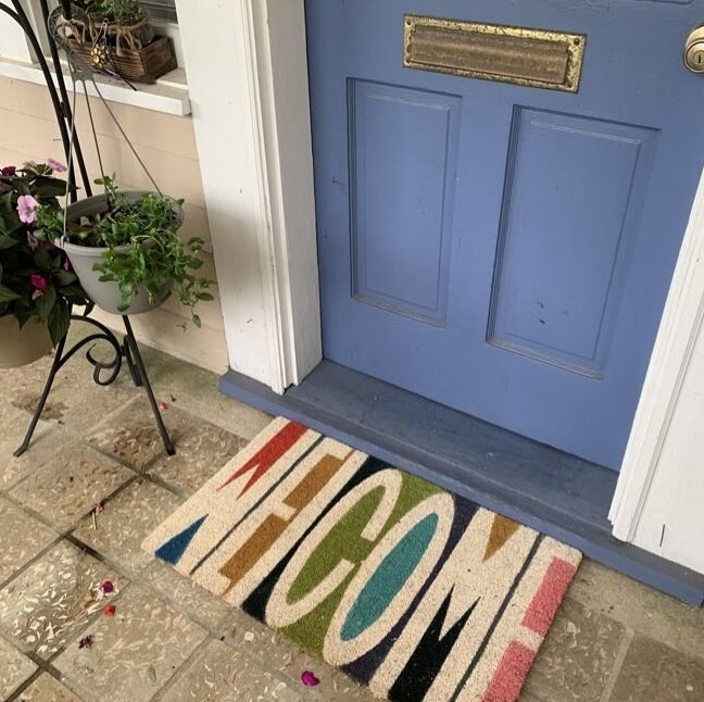 the rainbow-colored welcome mat in front of a reviewer's door