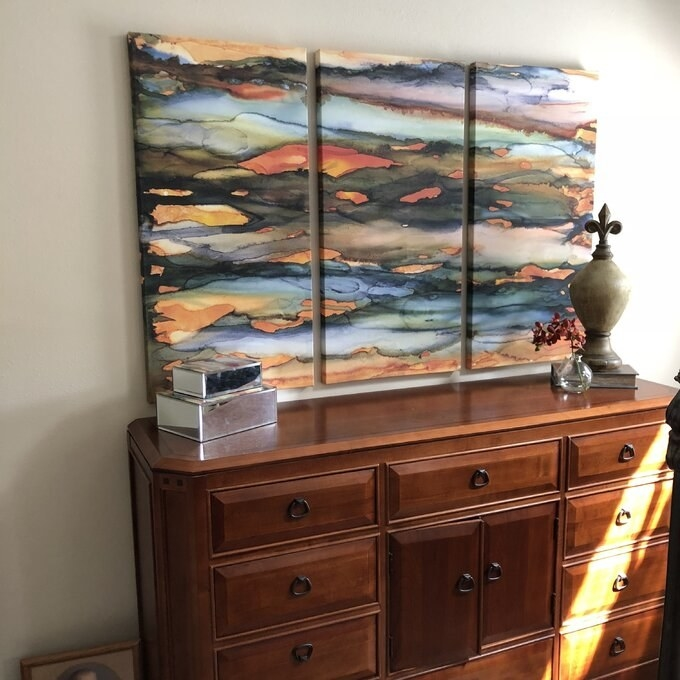 a reviewer's three paintings with orange, blue and green paint