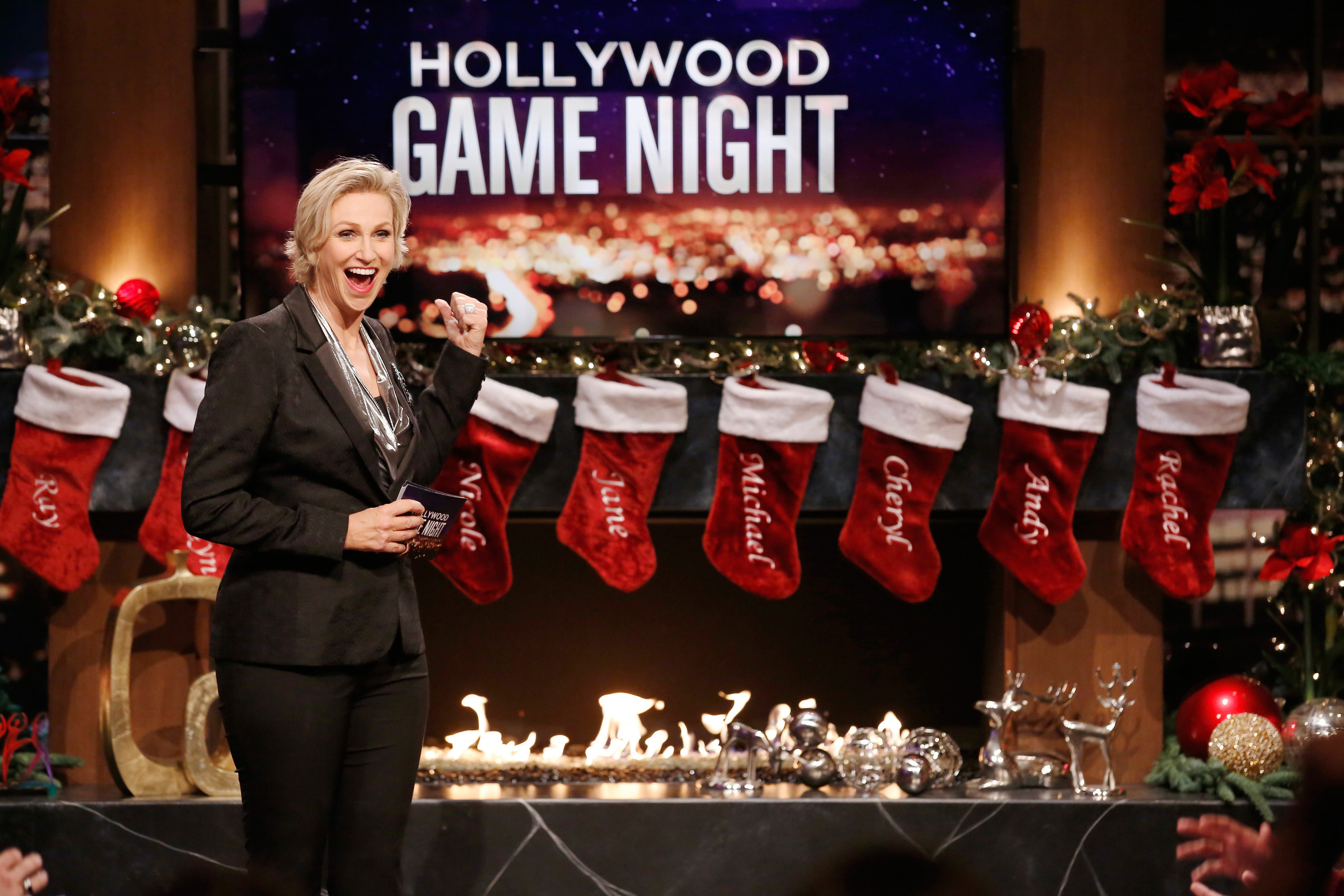 Jane Lynch hosting in front of a fireplace with stockings