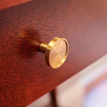 brass knob on a dark wood