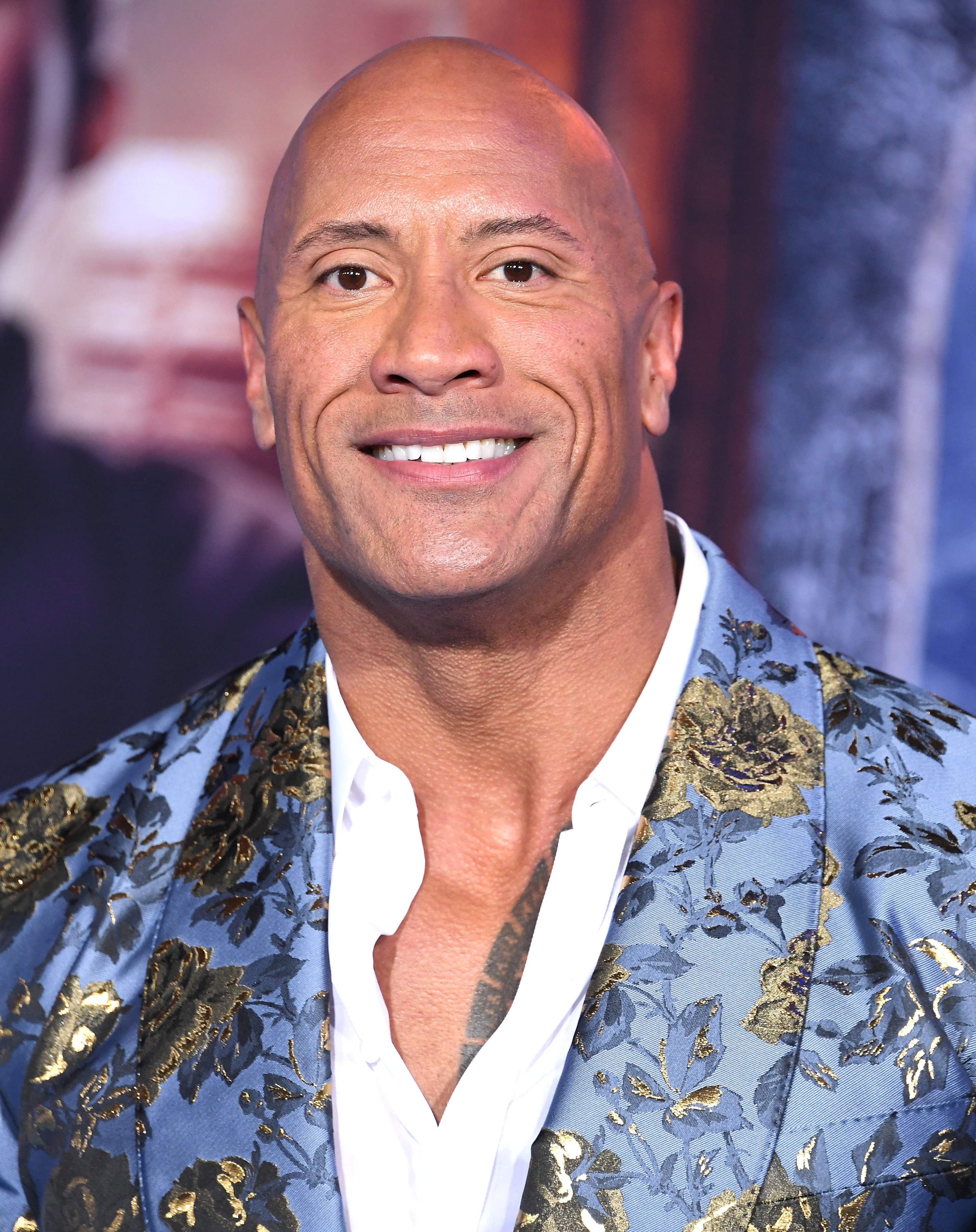 The Rock smiling as he wears a blue suit jacket with gold roses on it