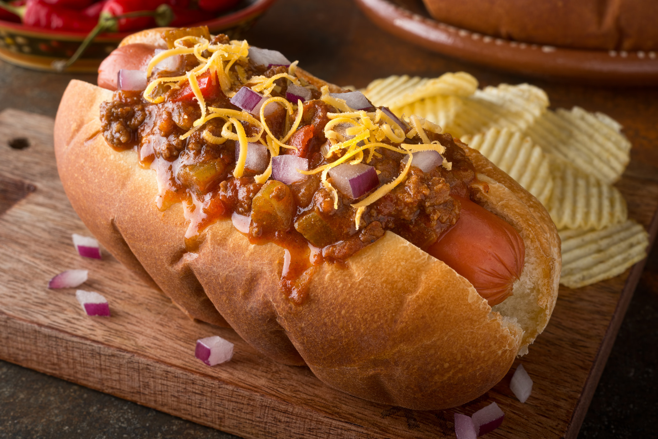 A hot dog topped with chili, cheese, and onions.