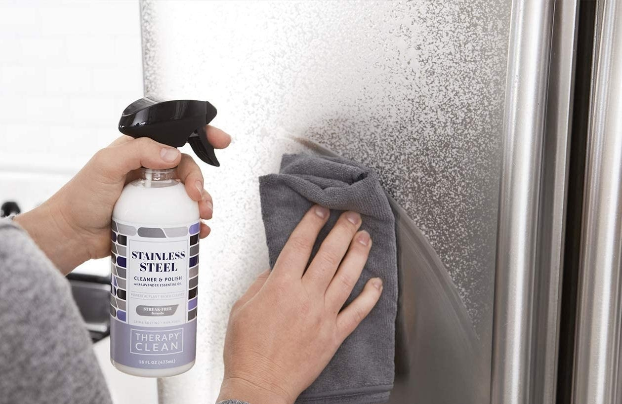 hand wiping fridge, sprayed with white cleaner,using a microfiber cloth