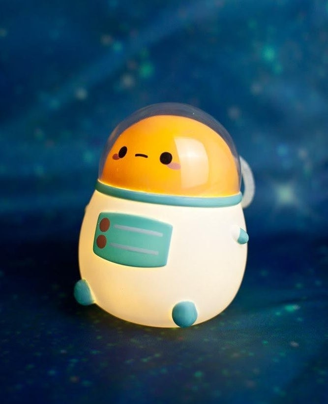 the small light shaped like a potato dressed in an astronaut suit, with a face and little arms and legs