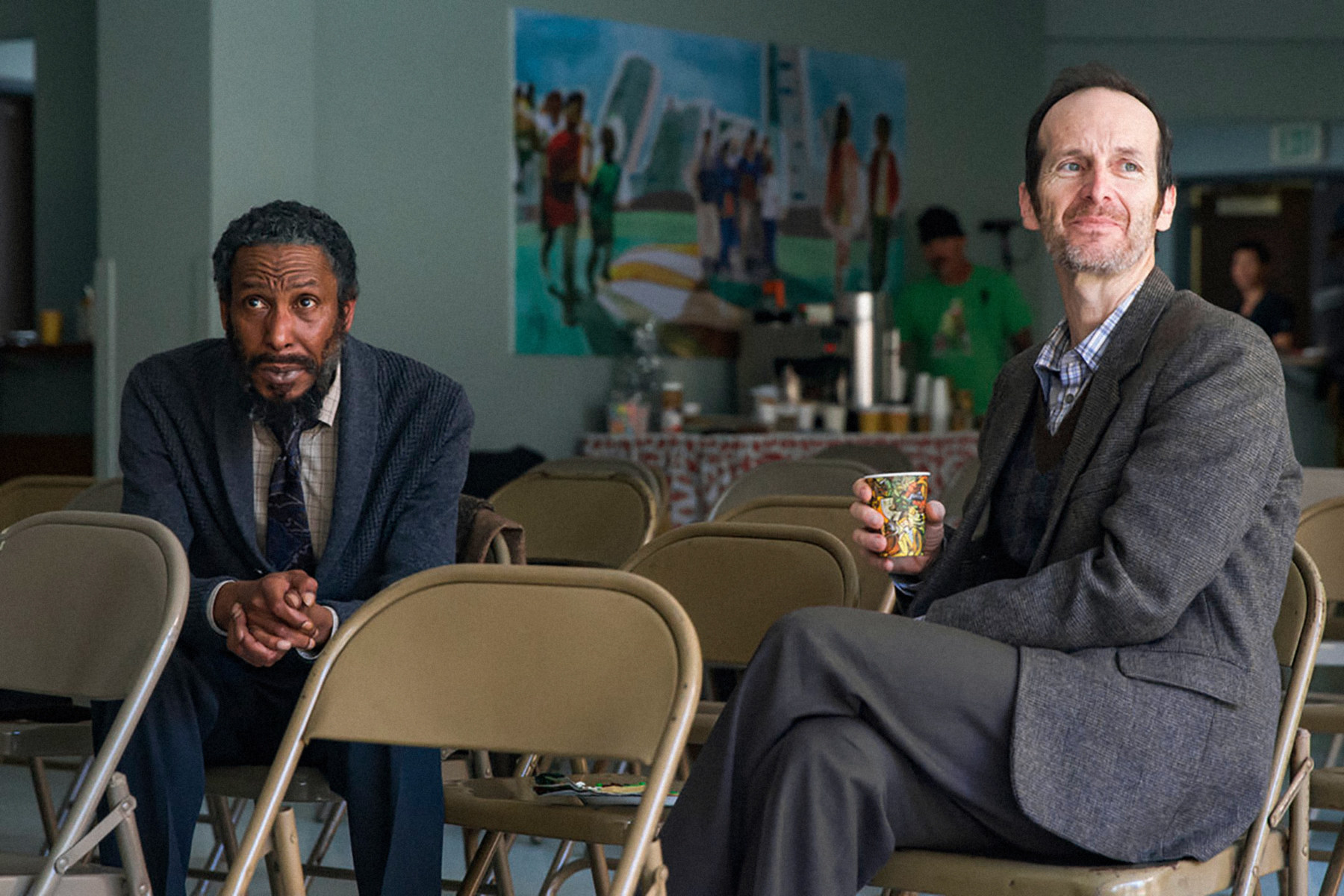 Ron Cephas Jones and Denis O'Hare sitting on folding chairs