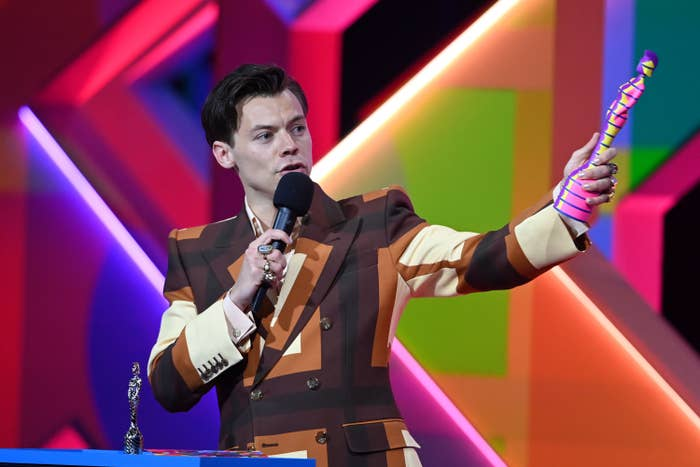 Harry holds up his award while giving his speech
