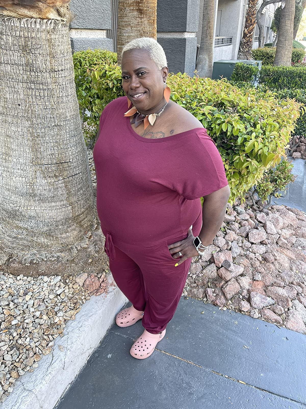 Reviewer wearing an off the shoulder burgundy jump suit with tie waist