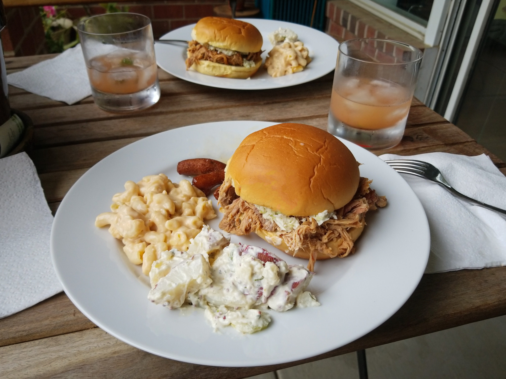 A pulled pork sandwich with slaw and sides of potato salad and mac 'n' cheese.