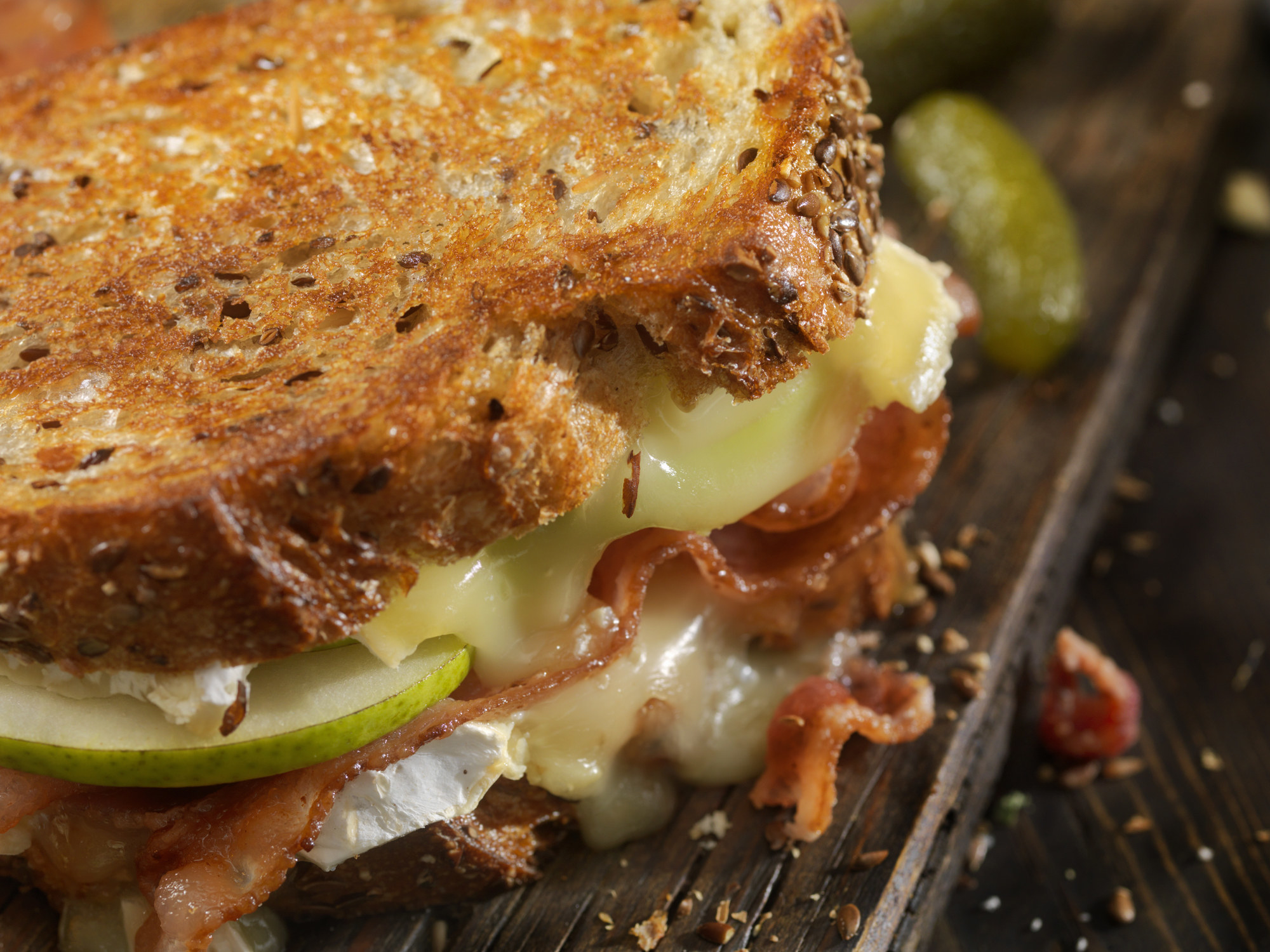 A gooey grilled cheese sandwich with apple and bacon.
