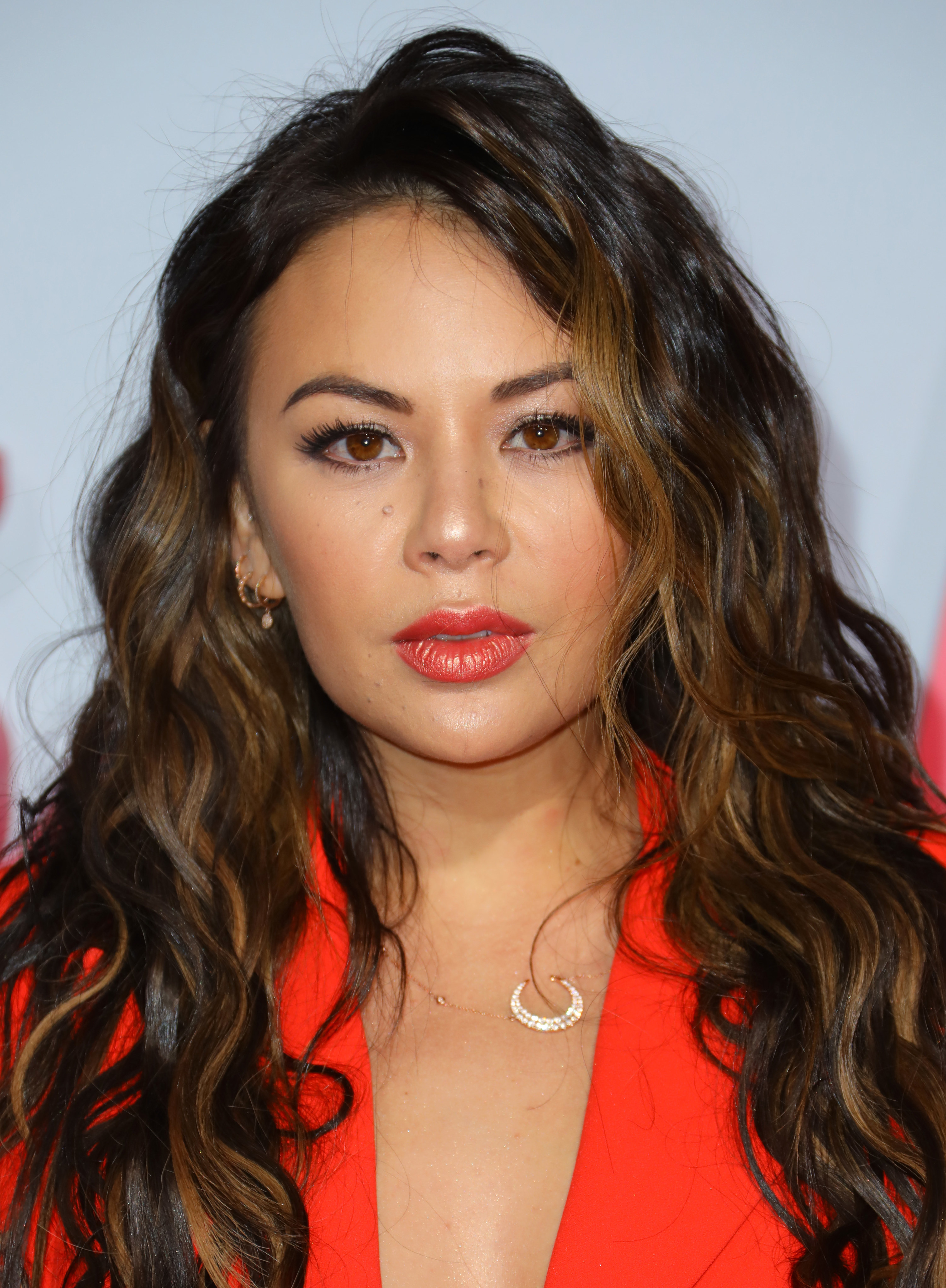 Janel Parrish wears a bold coral lip and matching blazer with her hair in long, loose waves