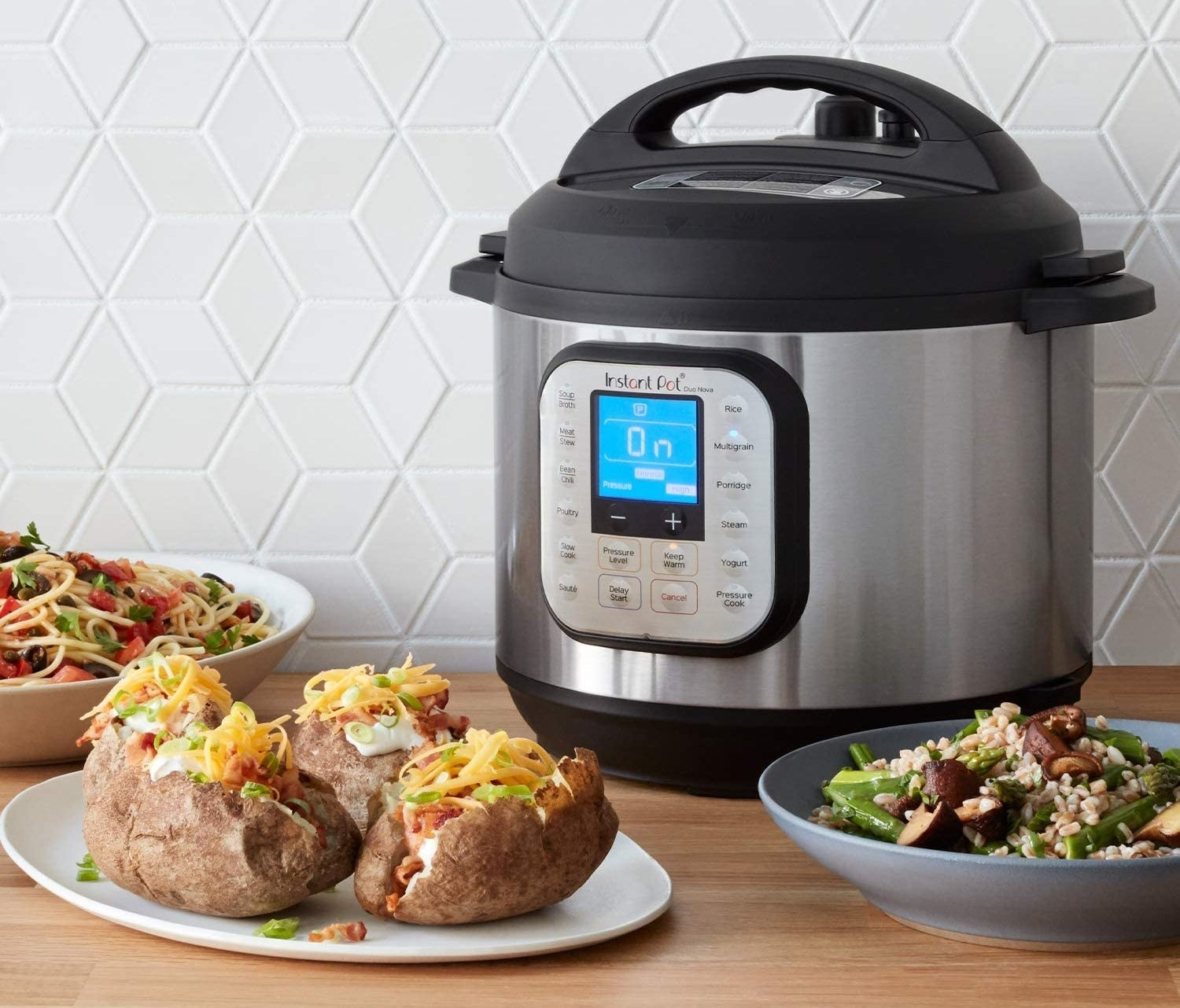 Instant pot surrounded by a pasta dish, baked potatoes, and a green beans and rice dish
