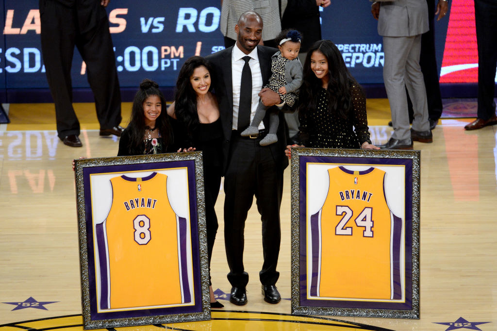 The Bryant family stands on a basketball court accepting a framed jersey of Bryant's