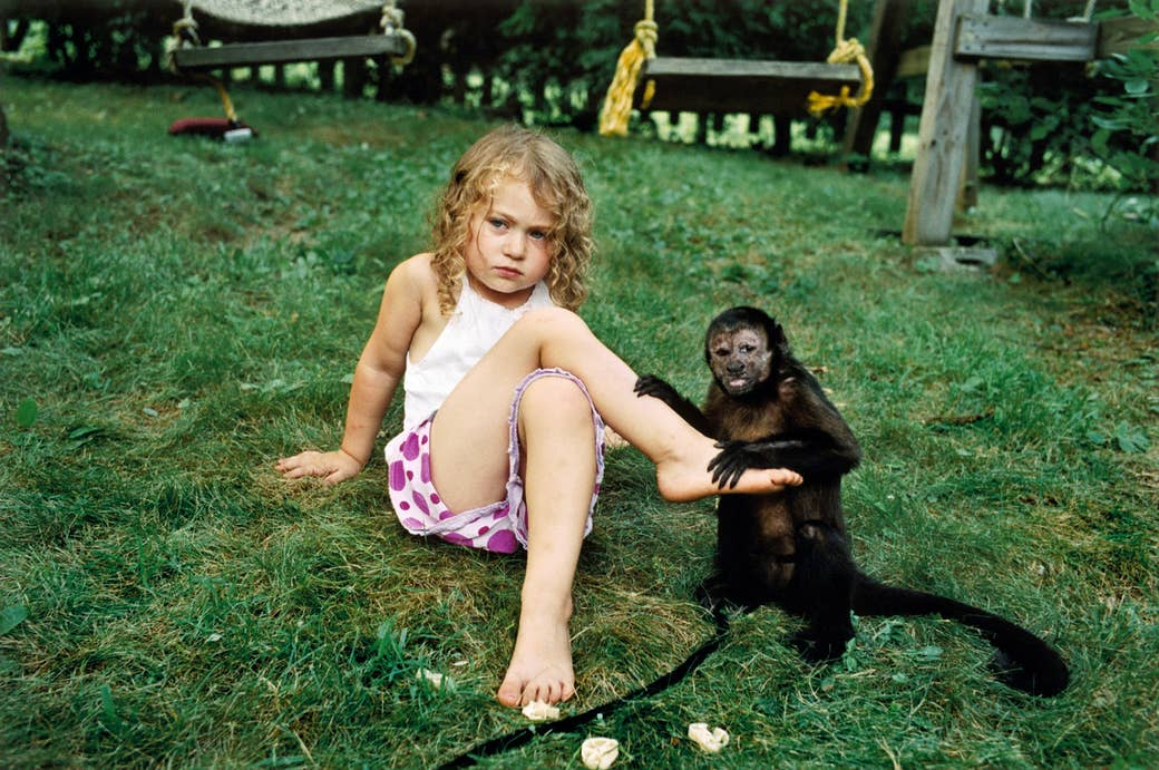 A young girl sits on the ground beside a small monkey, whose hands are on her shin and foot