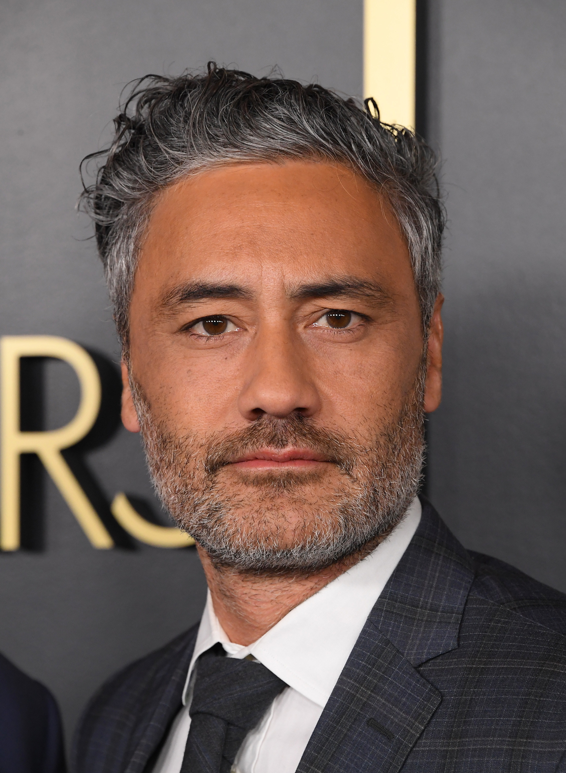 Taika Waititi looks directly at the camera in a suit at an award show
