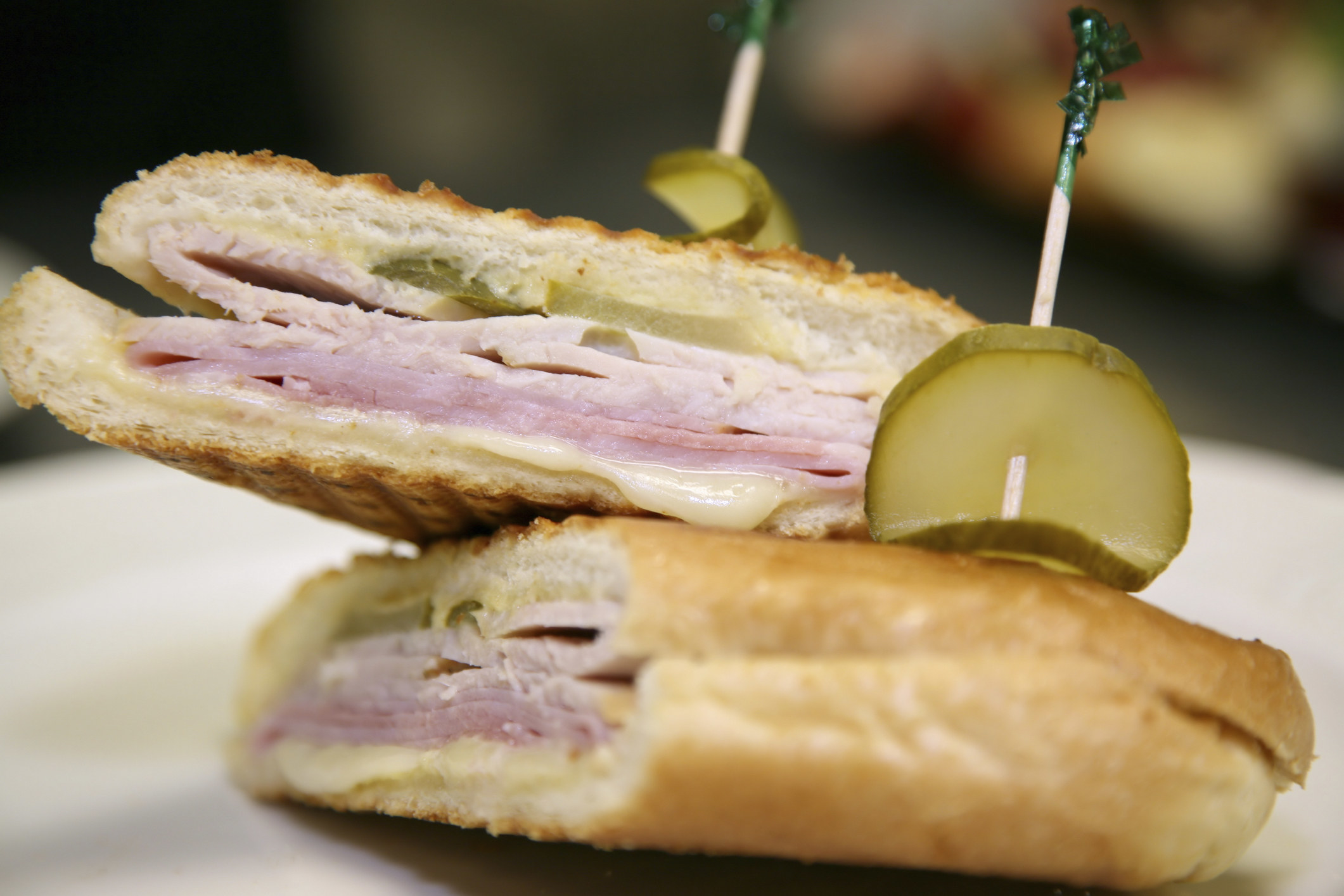 A cuban sandwich topped with pickles.