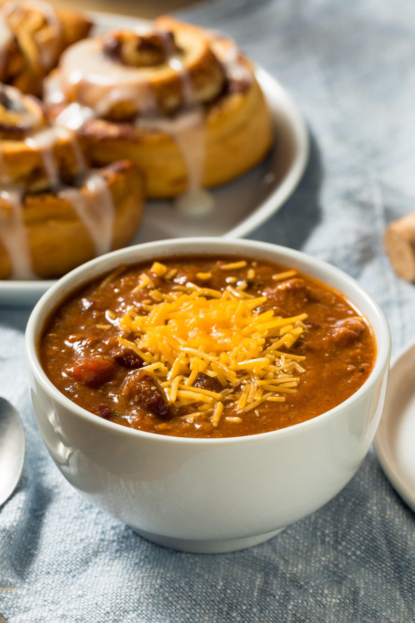 A bowl of chili and sweet cinnamon rolls.
