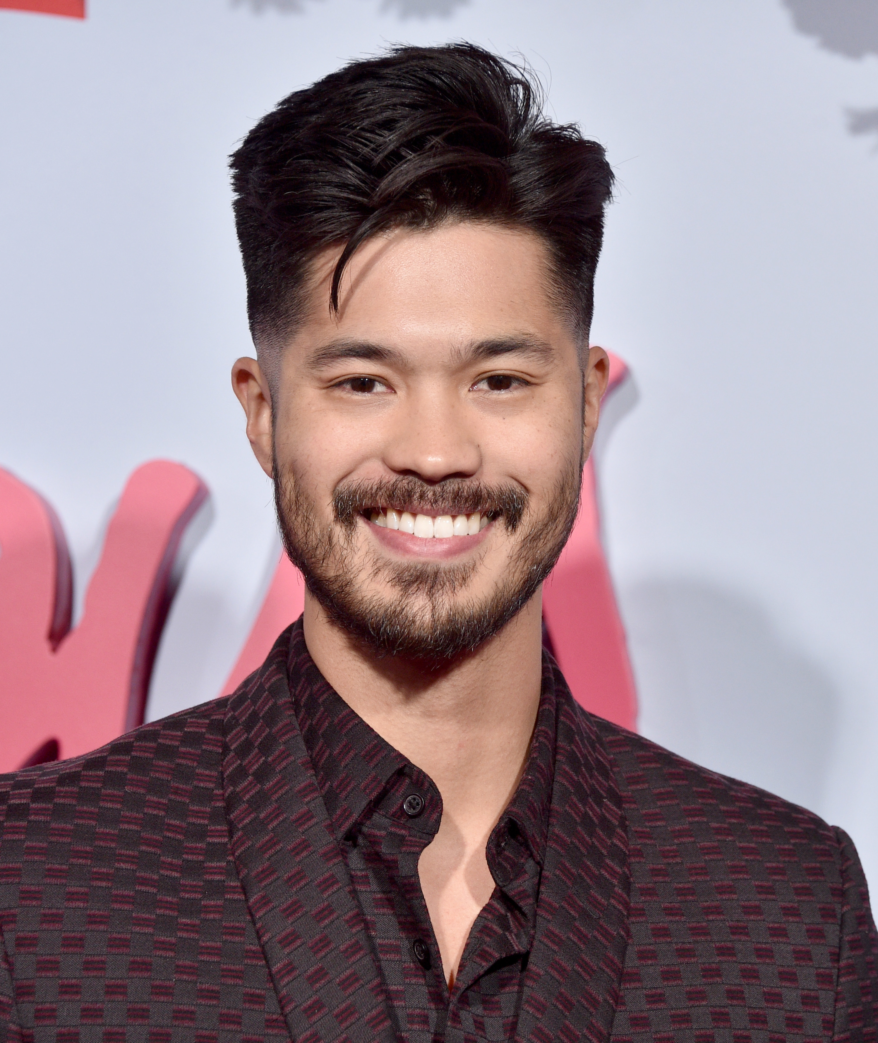 Ross Butler smiles in a matching suit and shirt