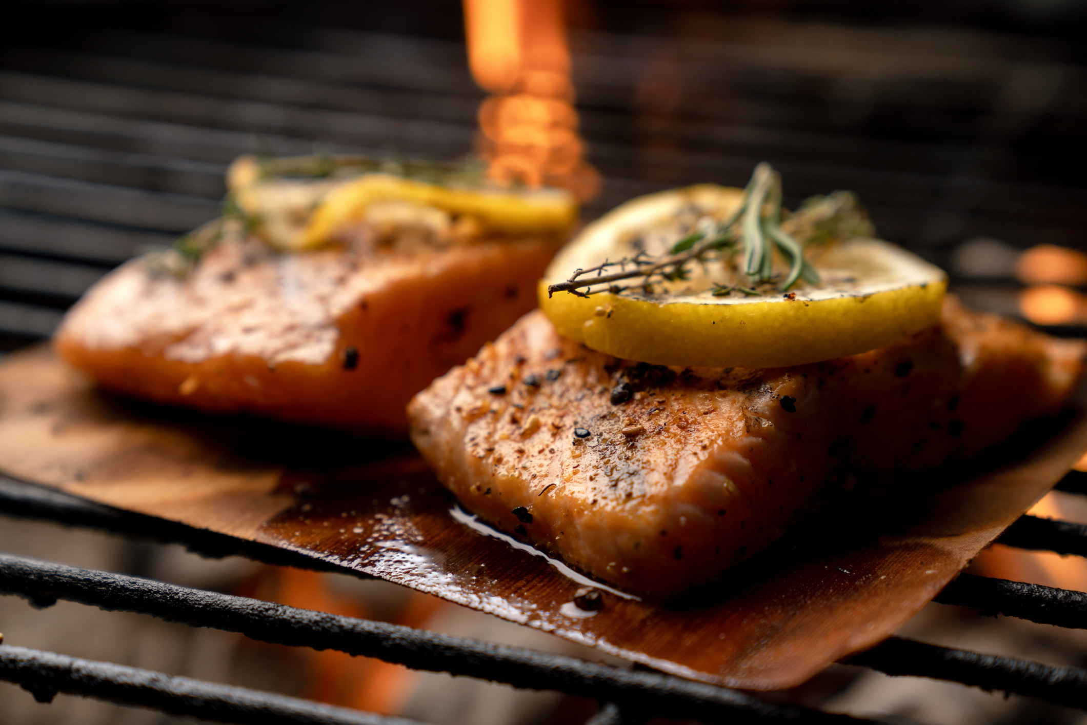 Two pieces of salmon on a wooden plank.