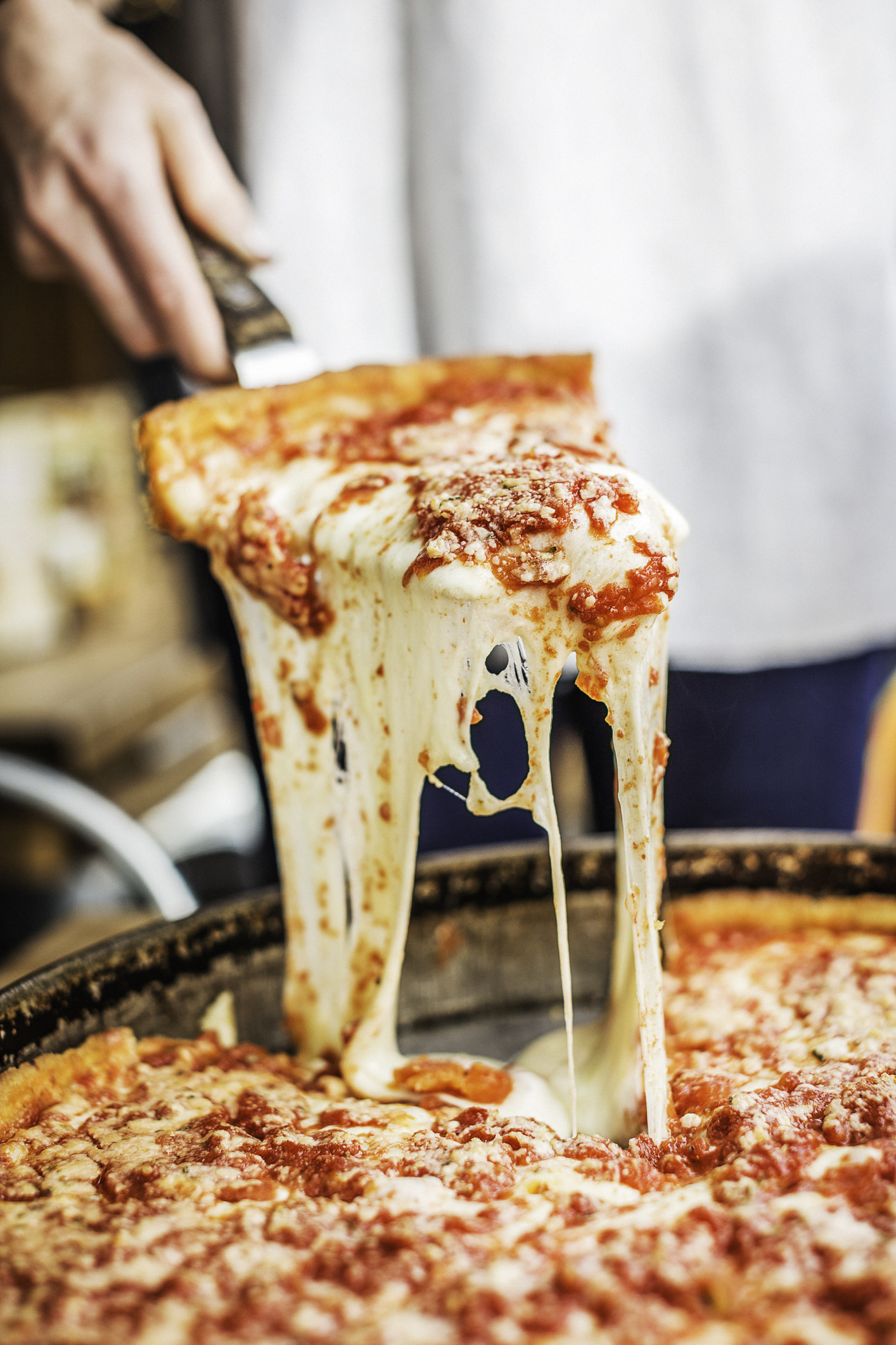 Serving a slice of cheesy, deep dish pizza.
