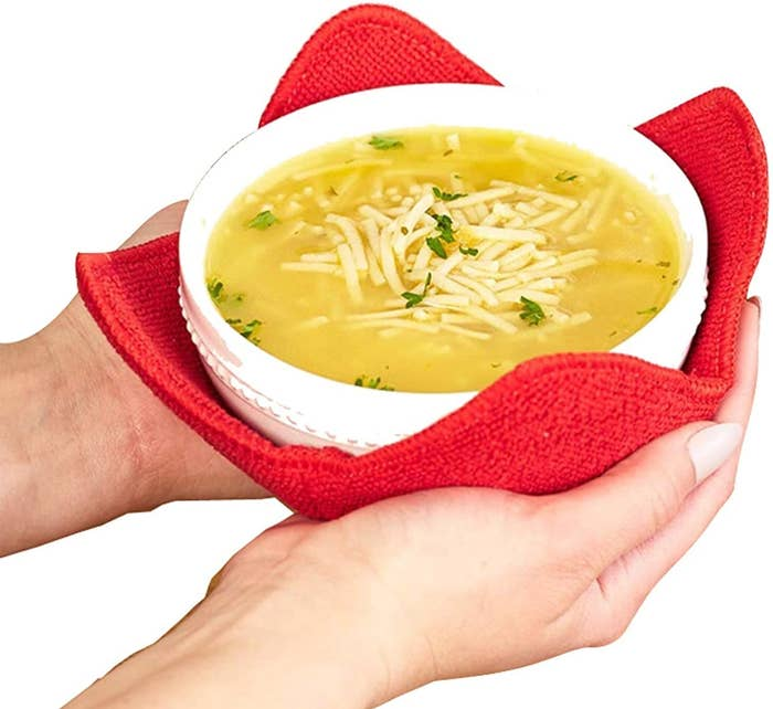 A pair of hands holding a bowl that's resting in the red bowl hugger
