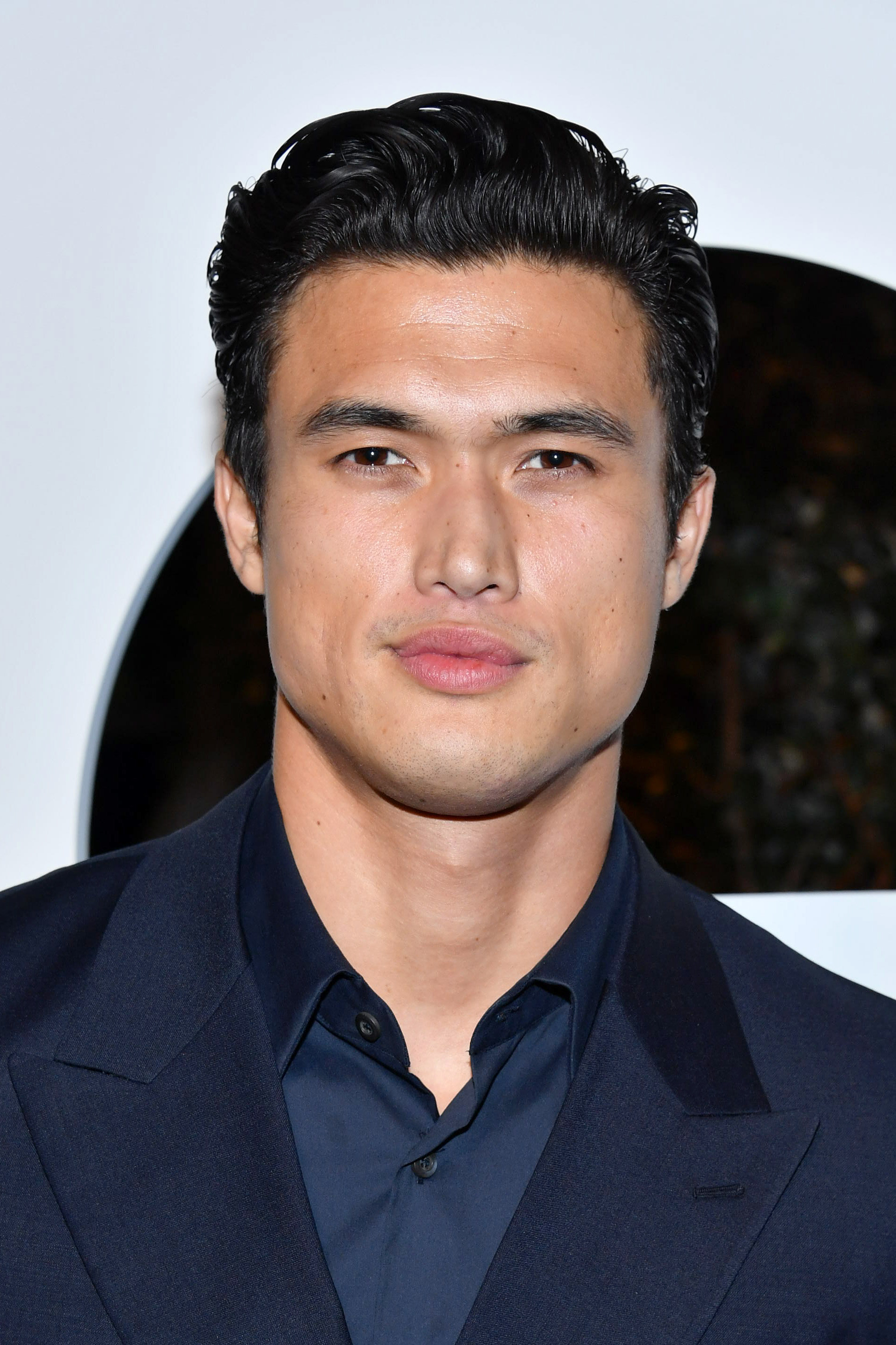 Charles Melton smiles in a navy suit