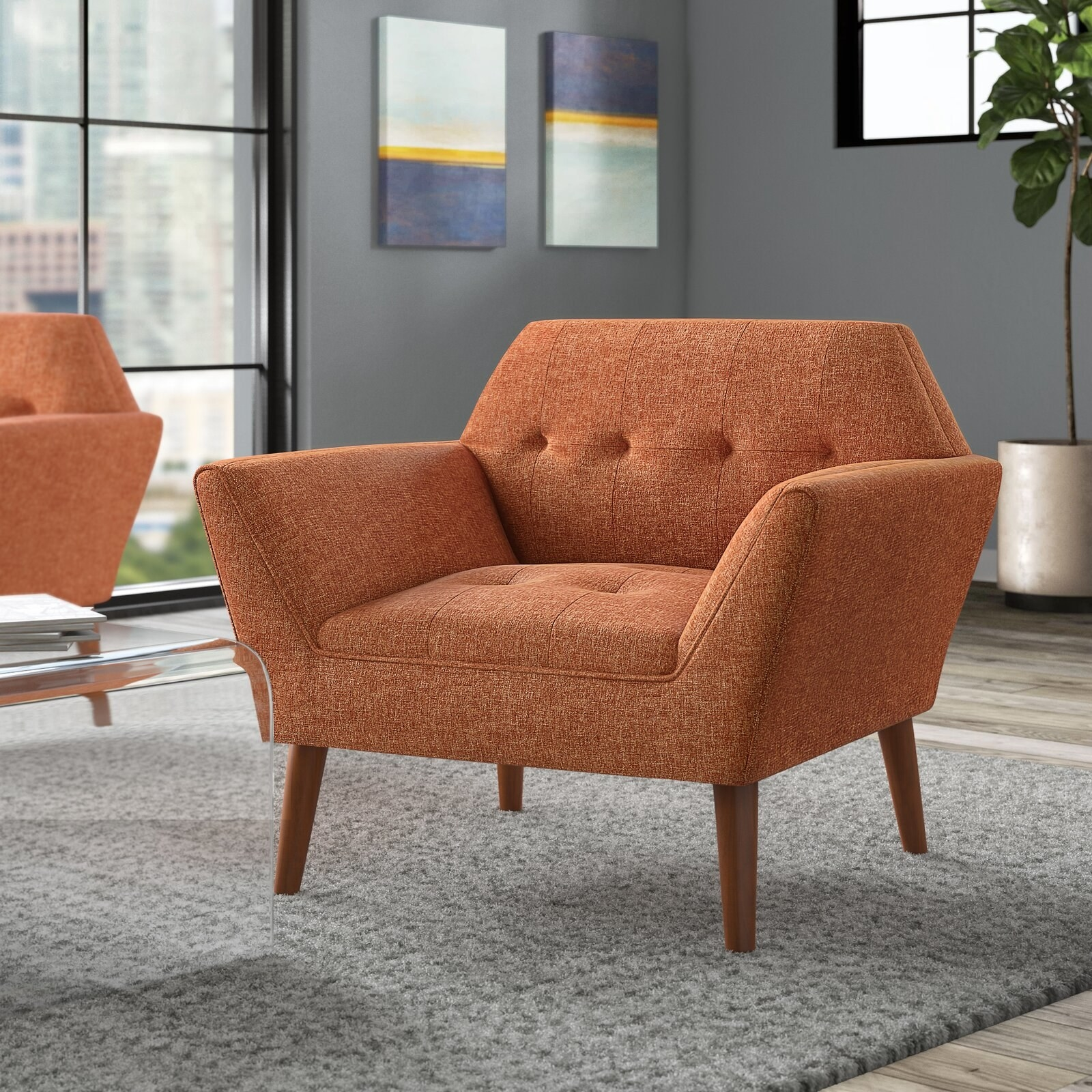 The chair, which has a hexagonal back panel and wooden splayed legs, in orange